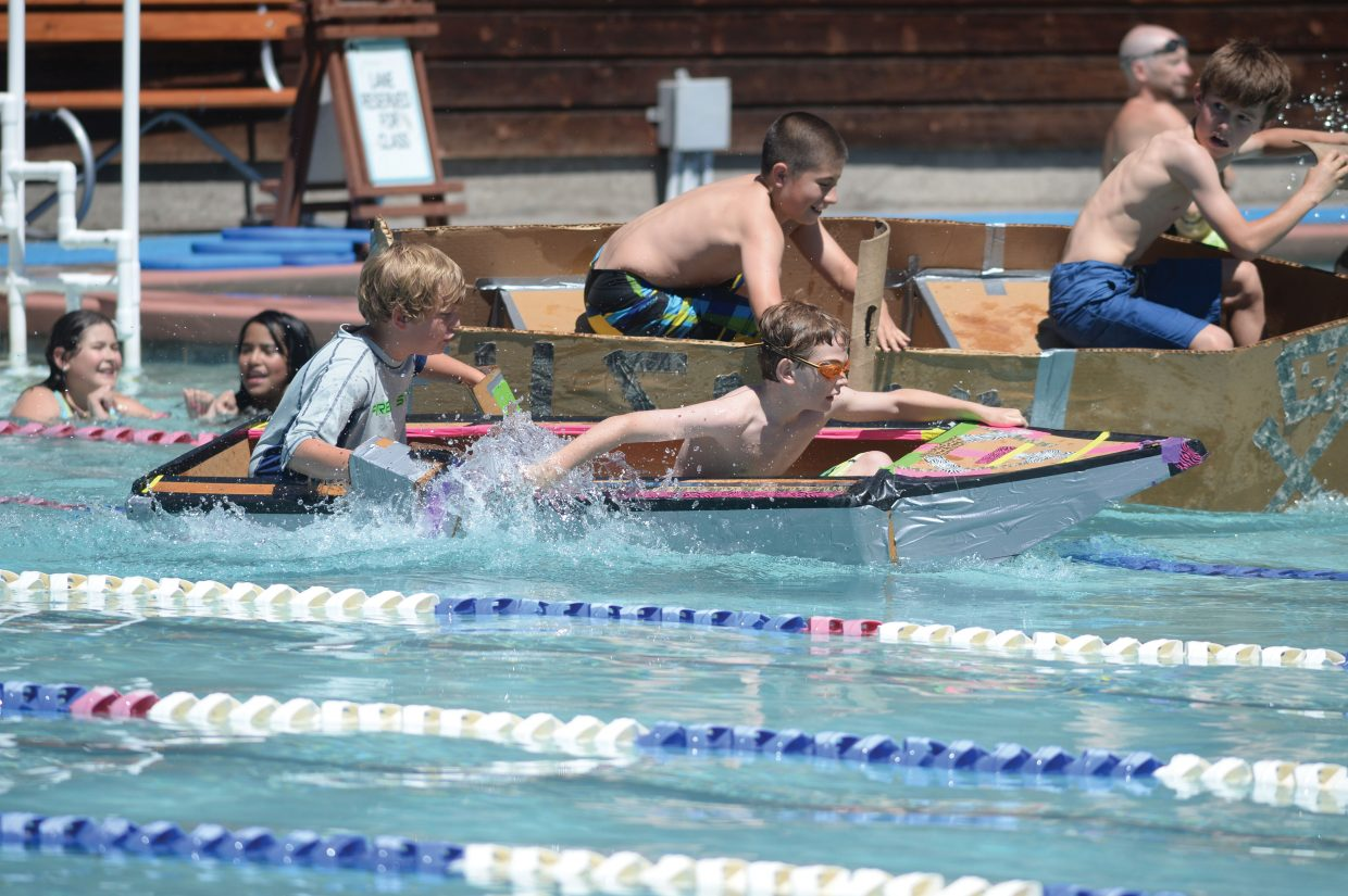 Soda Creek Elementary School fifth-graders Tommy Mewborn, front, and Jack Becker paddle for the other side of the pool during the annual Cardboard Classic race Wednesday at the Old Town Hot Springs.