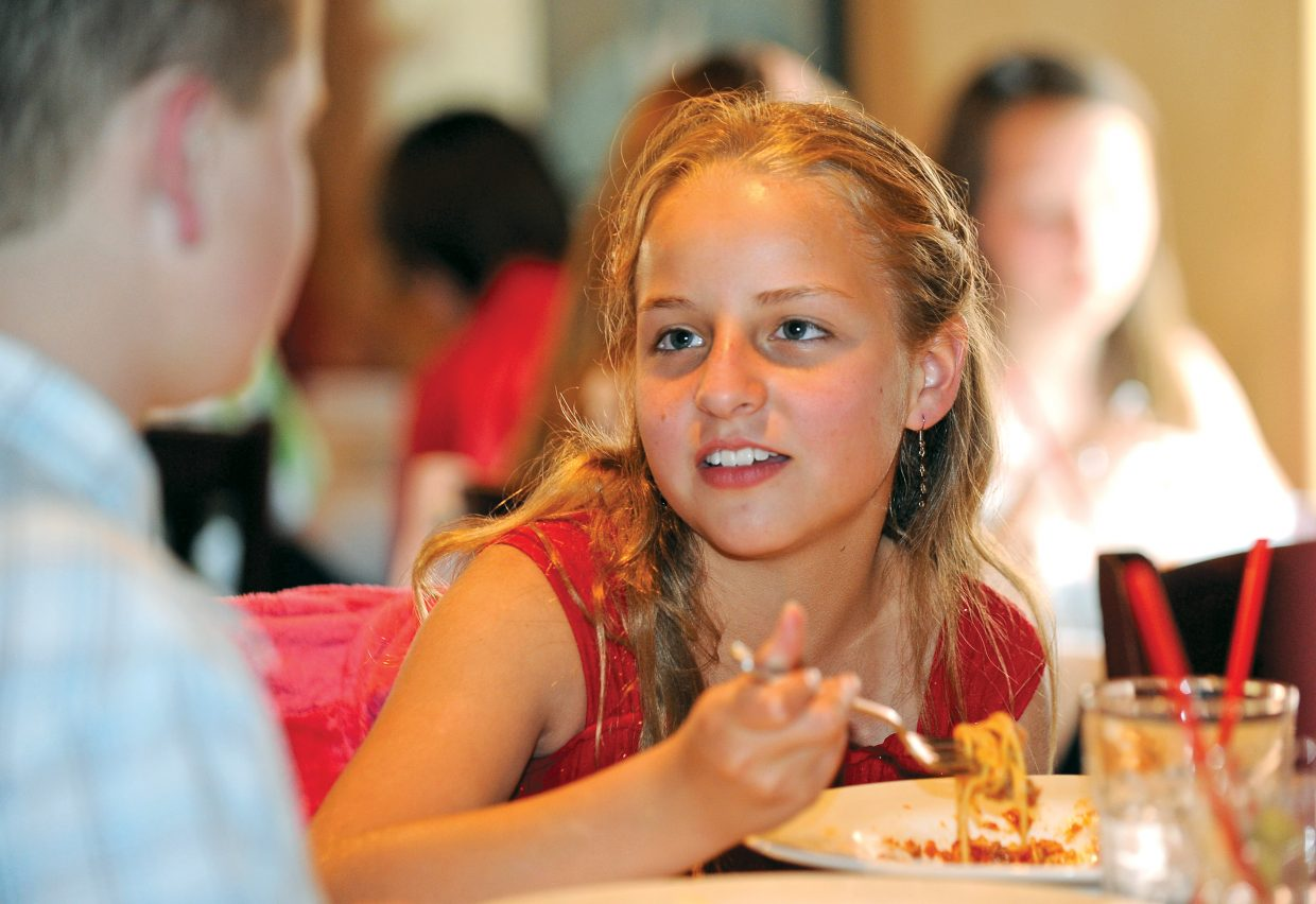 Fifth grade student Paula Effinger listens during a conversation with a classmate while taking part in the formal luncheon Thursday at Mambo Italiano. The luncheon is the culmination of Molly Manners etiquette lessons taught by Molly Hayes. The meal also is a celebration for the children who are making the transition to middle school.