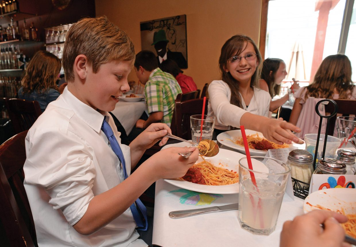 Soda Creek Elementary student Jackson Metzler enjoys lunch with his classmates during the fifth grade formal luncheon Thursday at Mambo Italiano. The luncheon is the culmination of Molly Manners etiquette lessons taught by Molly Hayes. The meal also is a celebration for the children who are making the transition to middle school.