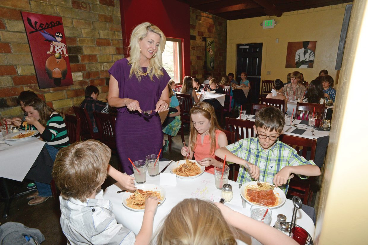 Molly Hayes speaks with fifth grade students from Soda Creek Elementary School on Thursday about proper manners during the a formal luncheon at Mambo Italiano.