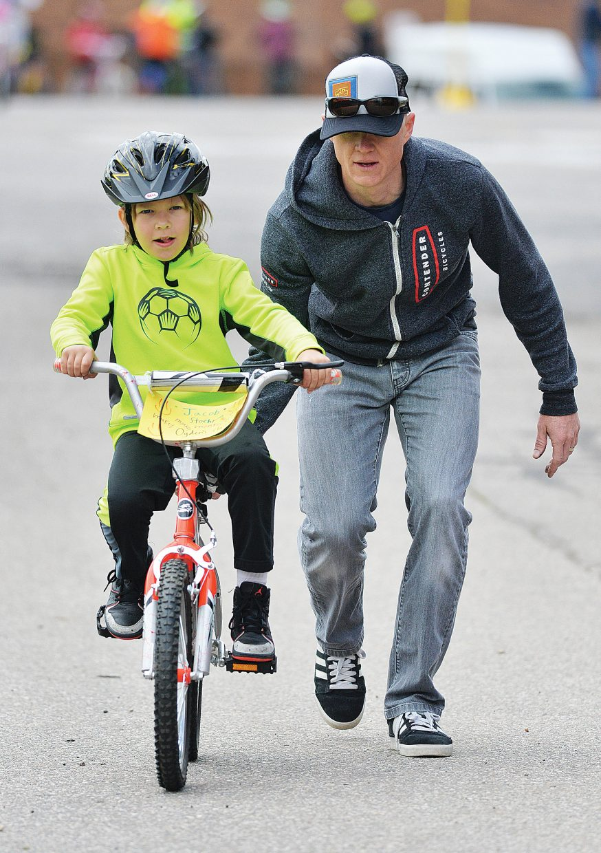 Volunteer Simon Fryer helps Strawberry Park Elementary student Jacob Stoehr learn to ride a bike during the Strawberry Park Elementary School's bike rally Friday morning. Volunteers, including a group of Moots, set up a number of stations hoping to remind elementary students about riding safely this spring and summer.