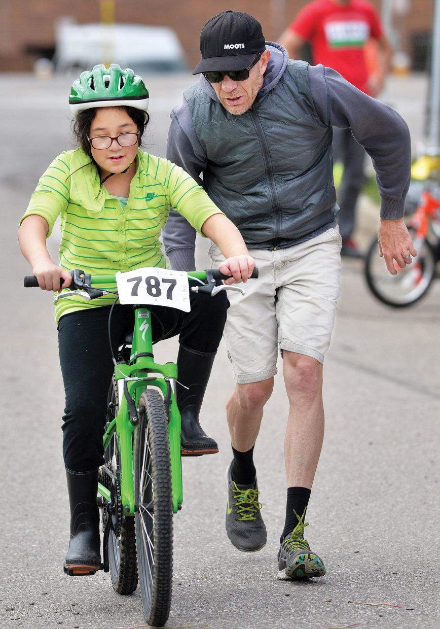 Moots employee Jon Cariveau helps Strawberry Park Elementary student Monica Ramirez-Luna learn to ride a bike during the Strawberry Park Elementary School's bike rally Friday morning. Volunteers, including a group of Moots, set up a number of stations hoping to remind elementary students about riding safely this spring and summer.