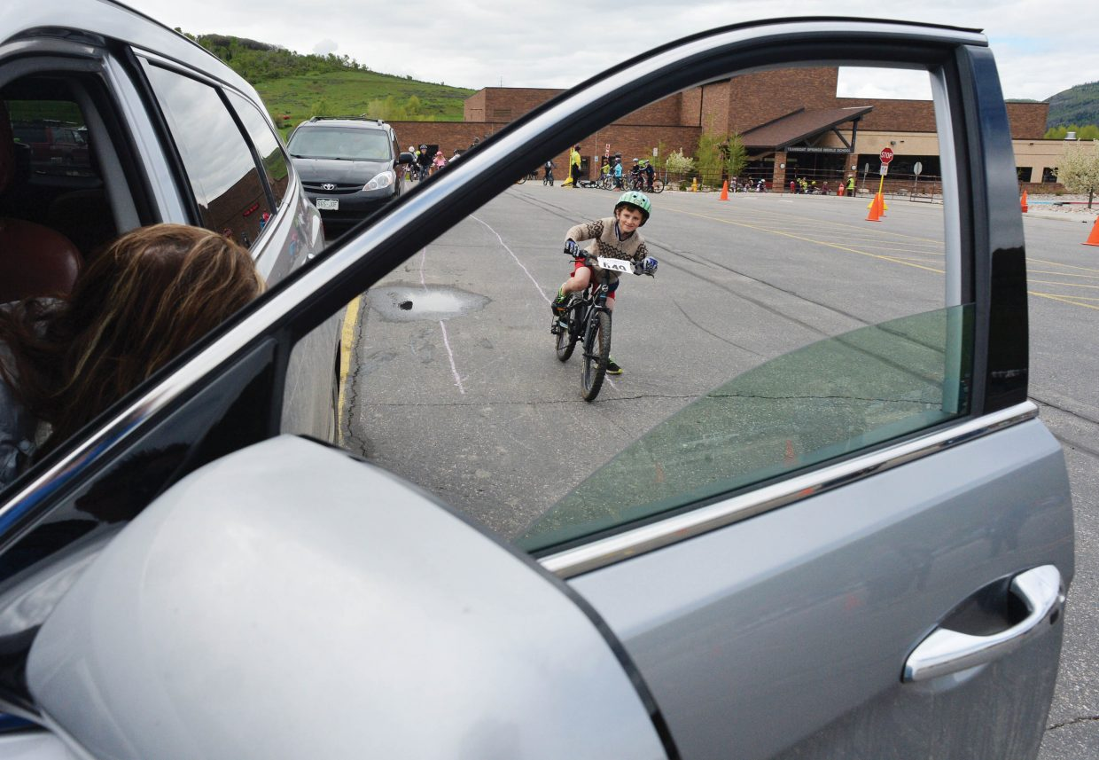 Strawberry Park Elementary School second grader Alexander Craig comes to a stop for an opened car door. It was just one of the many lessons passed along at the Strawberry Park Elementary School Bike Rally Friday morning. Volunteers, including a group of Moots, set up a number of stations hoping to remind elementary students about riding safely this spring and summer.
