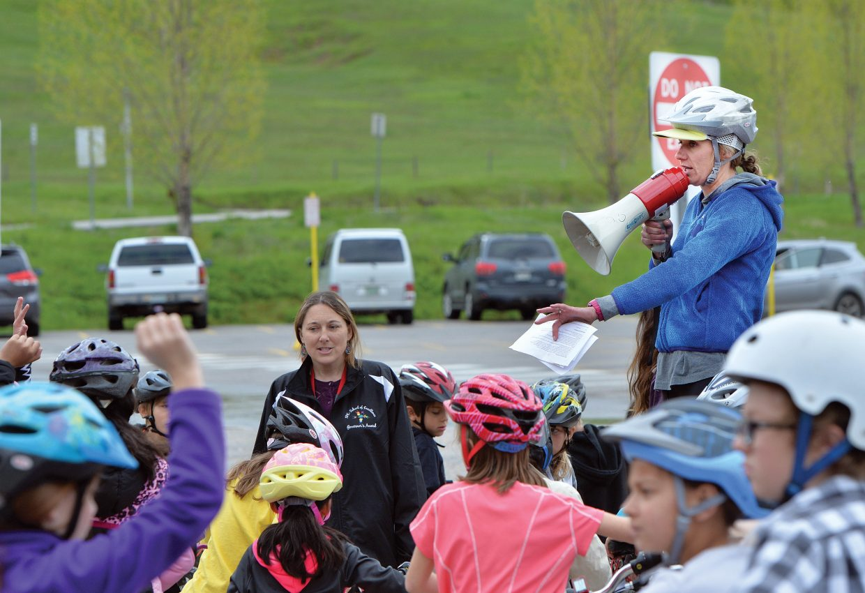 Strawberry Park Elementary School physical education teacher Allison Sabat addresses the second and third graders Friday at the start of the school's annual bike rally, which is put on with the help of Safe Routes to School. Volunteers, including a group of Moots Cycles in Steamboat Springs, set up and ran a number of stations hoping to remind elementary students about riding safely this spring and summer.