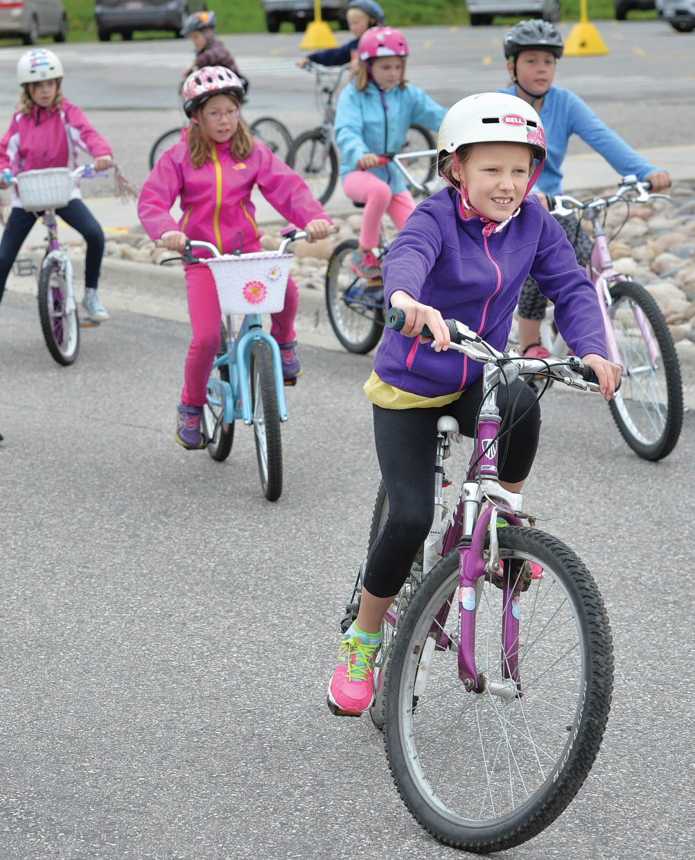 Strawberry Park Elementary School third grader Kaelyn Radway heads to one of several stations at this year's Strawberry Park Bike Rally Friday morning. Volunteers, including a group of Moots, set up a number of stations hoping to remind elementary students about riding safely this spring and summer.