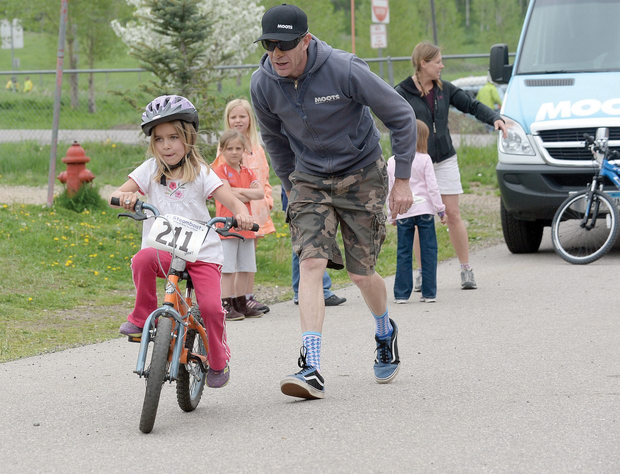Strawberry Park Elementary School kindergartner Julia Crocker gets a helping hand from Jon Cariveau, of Moots, on Friday morning at the school's annual bike rally. It was Crocker's first time on a bike. The rally is a chance for elementary students to get out on their bikes and learn a few things about safety as summer arrives in the Yampa Valley.