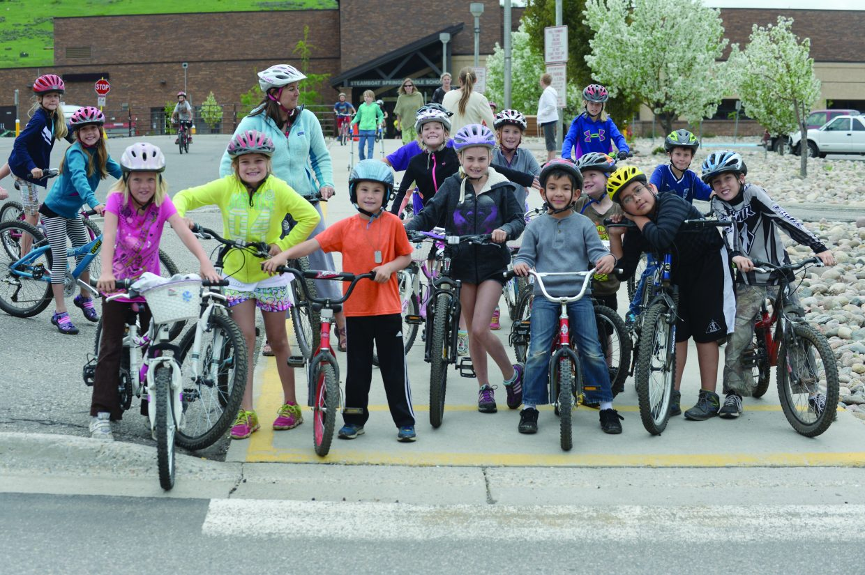 Strawberry Park Elementary School students wait to cross the street during a bike rally at the school Friday morning. The school encouraged its students to bike or hike to school, and then offered a fun day where the young riders could learn about their bikes, about how to be safe on the road and other basic skills to improve their bike riding.