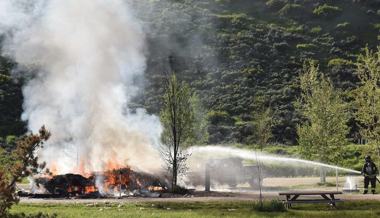 Steamboat Springs Fire Rescue firefighters use a hose to dowse the flames that resulted from an explosion at the Eagle Soaring RV Park west of Steamboat Springs. The explosion sent one man to the hospital Tuesday evening.