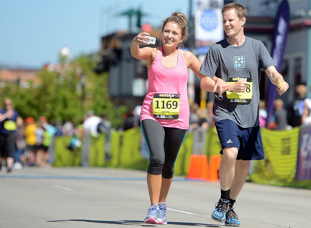 Kyrstie Cox and Ben Cox pull together for a photo as they cross the finish line of Sunday's Steamboat Marathon.