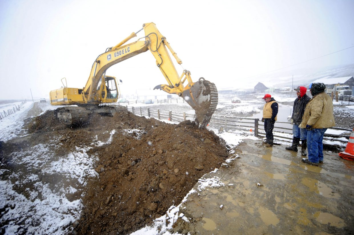 Routt County Road and Bridge workers install a culvert Tuesday to help alleviate flooding in 2011. The county has completed a salary survey that tells them some county workers are paid above market rates, and some below market rates.