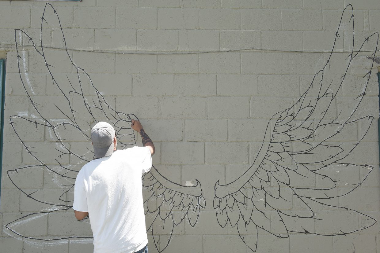 Artist Jeff Roth works on a new interactiv mural on the side of the Kali's building in downtown Steamboat Springs. The work was featured by an advisory group, led by the Steamboat Springs Arts Council, that led a walking tour Wednesday for members of the Colorado Creative Industries. The group is hoping to have the downtown area designated as an arts district.