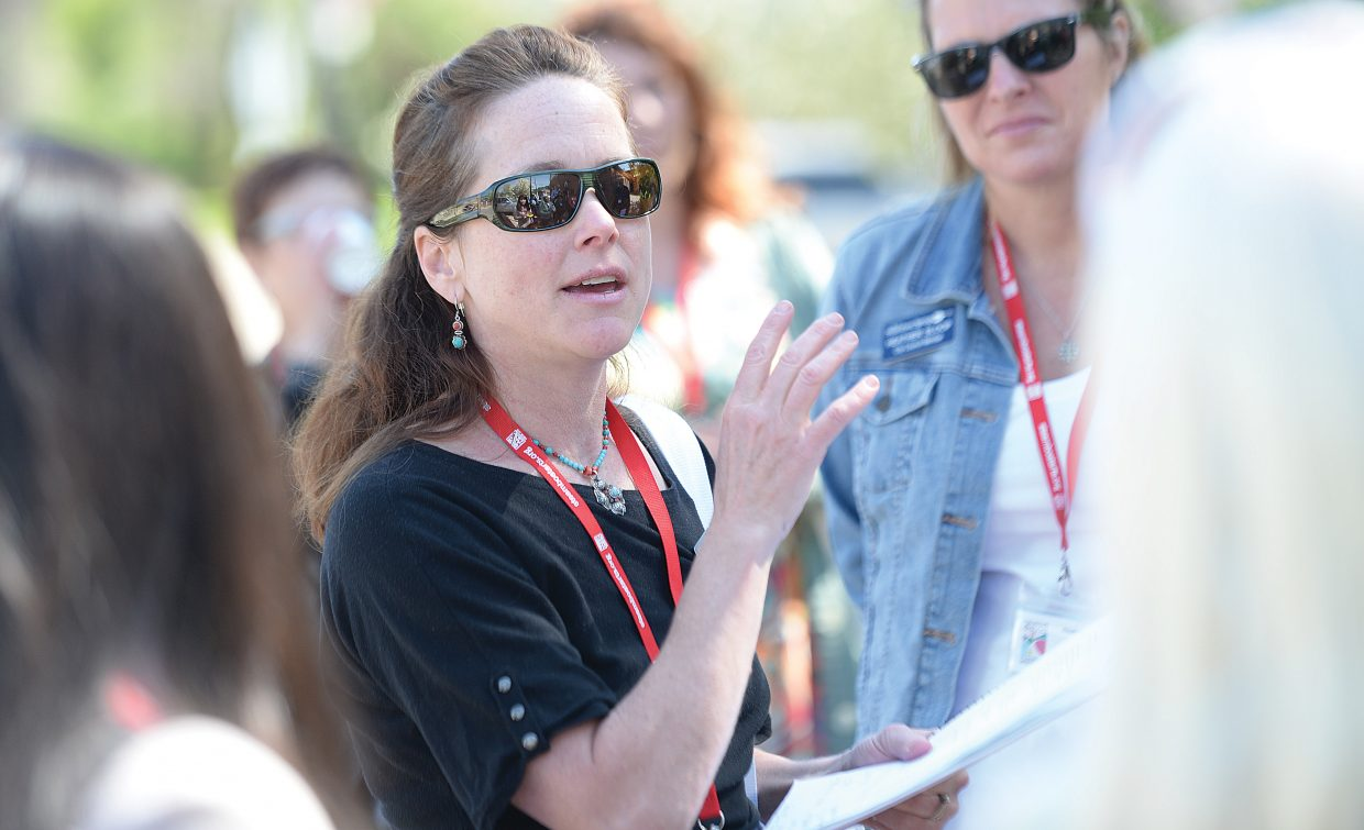 Candice Bannister adds a touch of history to a walking tour Wednesday for members of the Colorado Creative Industries. An advisory group is hoping to have the downtown area designated as an arts district.