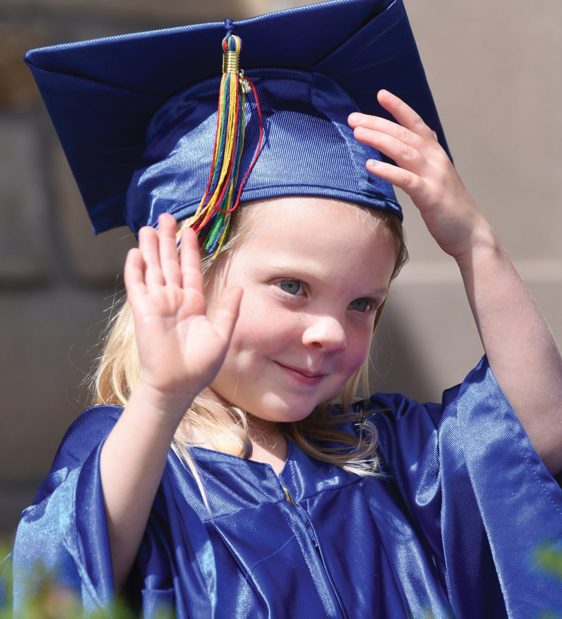 Holy Name Preschool student Kinsley Melland waves to her parents in the crowd during her graduation ceremony Thursday. Melland and her classmates will wave goodbye to preschool and head to kindergarten in the fall.