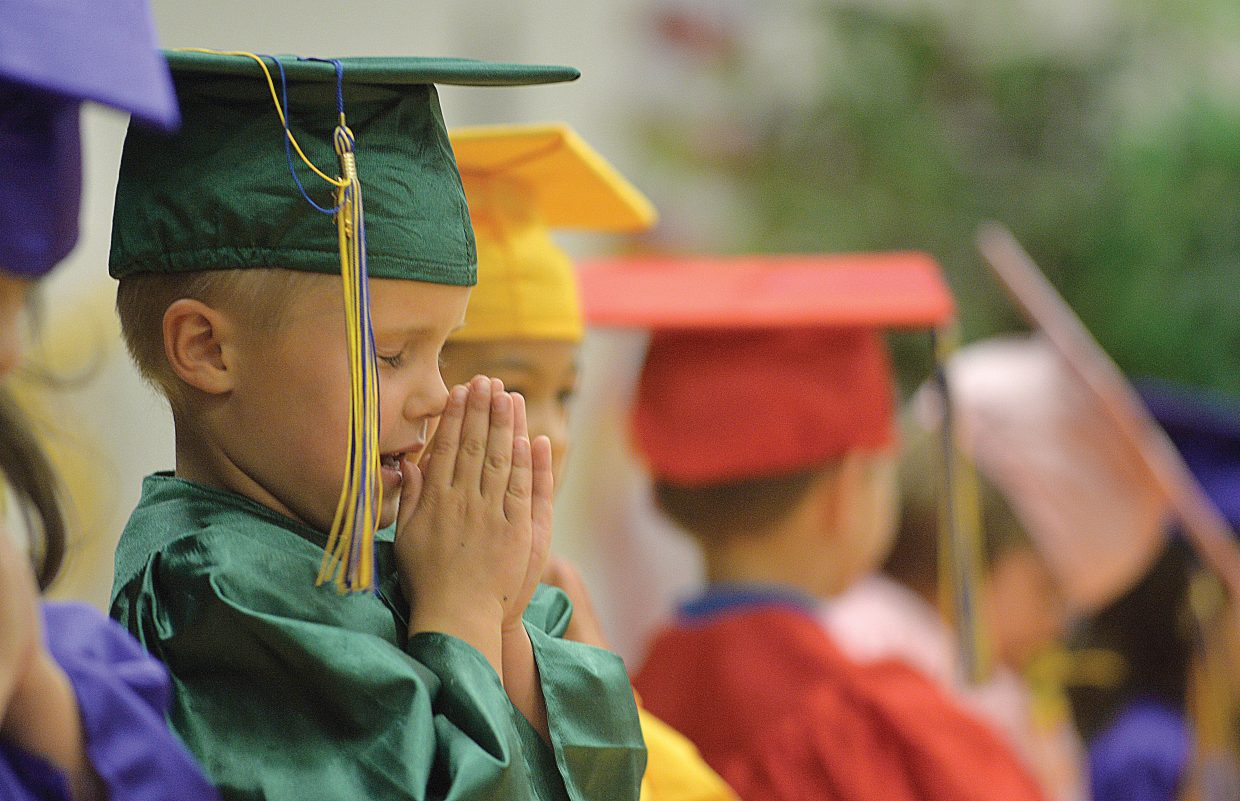 Kindergartner Marshall Moss says a prayer during the Heritage Christian School kindergarten graduation Tuesday afternoon at the school west of Steamboat Springs. Eleven students graduated and will move onto first grade next year.