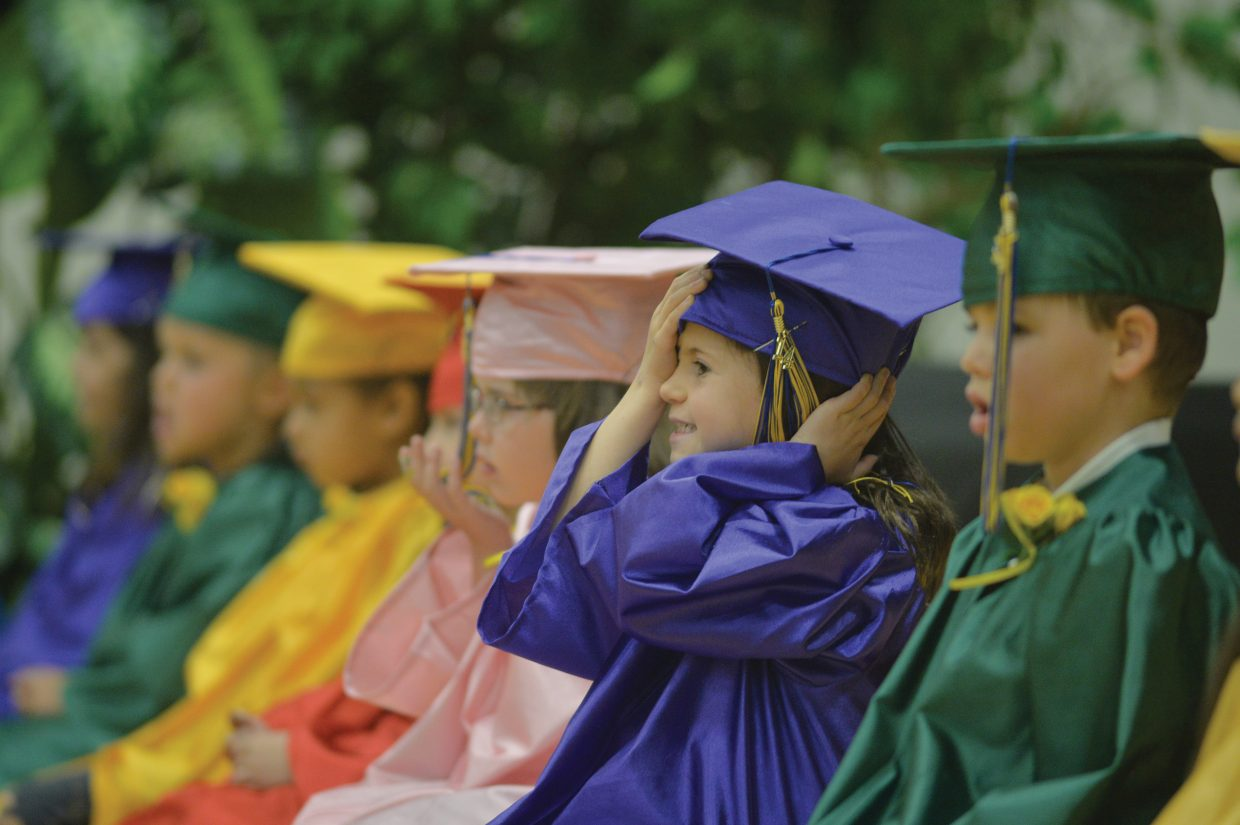 Kindergartner Ailie Strong adjusts her Mortarboard during the Heritage Christian School kindergarten graduation Tuesday afternoon at the school west of Steamboat Springs. Eleven students graduated and will move onto first grade next year.