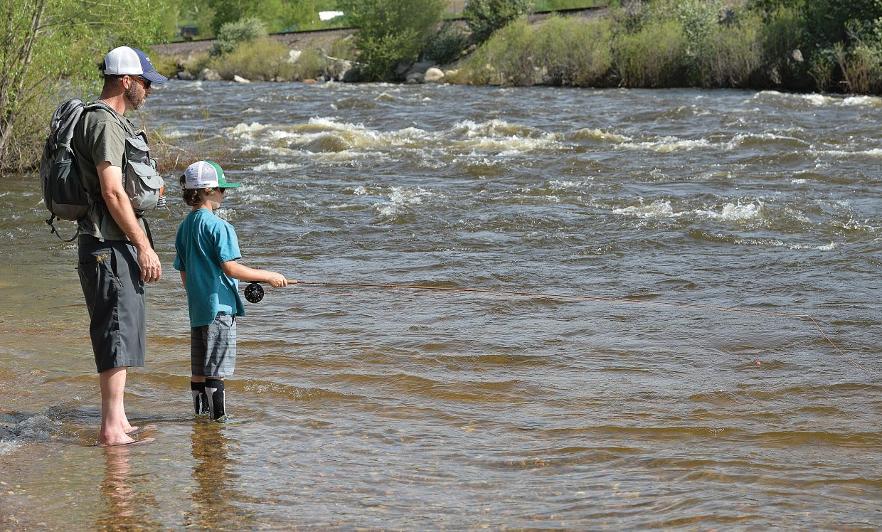 Caleb Franklin gives his son, Finneas, 8, a few tips while fishing on the Yampa River Wednesday afternoon. Caleb must be a good teacher, because just a few moments after this photo was taken, Finneas pulled a good-sized trout out of the river.