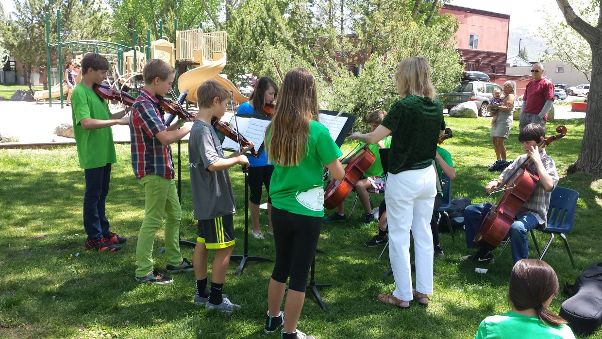 Sixth-, seventh- and eighth-graders from Emerald Mountain School play an impromptu concert at Little Toots Park. The students, who began playing stringed instruments in kindergarten, entertained the children and their parents at the park with a combination of pop tunes and classical music.