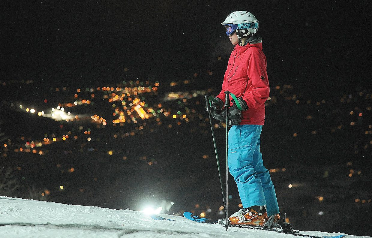 Night skier Andrew Petersen waits for friends at the top of the Christie Peak Express lift as the lights of Steamboat Springs create a colorful background. The ski area reportedly saw nearly 19,000 night skiers during the first season under the lights.