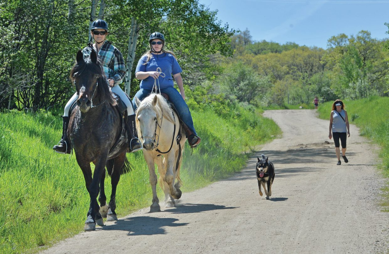Jan Willman, front, and Allison Keating, ride horses along the trials on Emerald Mountain in 2015.