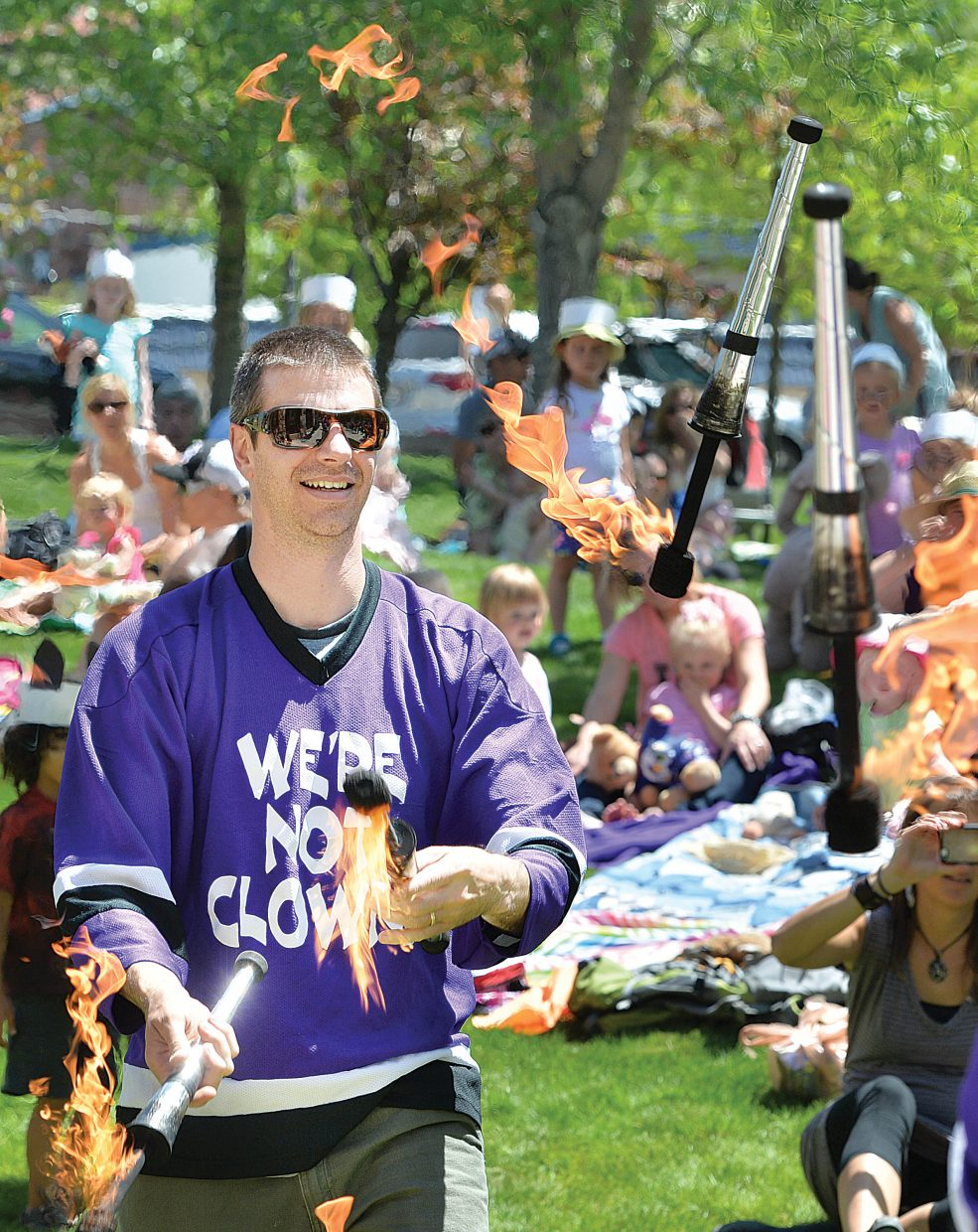 Kelly Anzalone, from We're Not Clowns, juggles flaming pins during the annual Teddy Bear Picnic at the Bud Werner Memorial Library Thursday morning. The event included entertainment from the Yampa Valley Boys and We're Not Clowns as well as face painting.