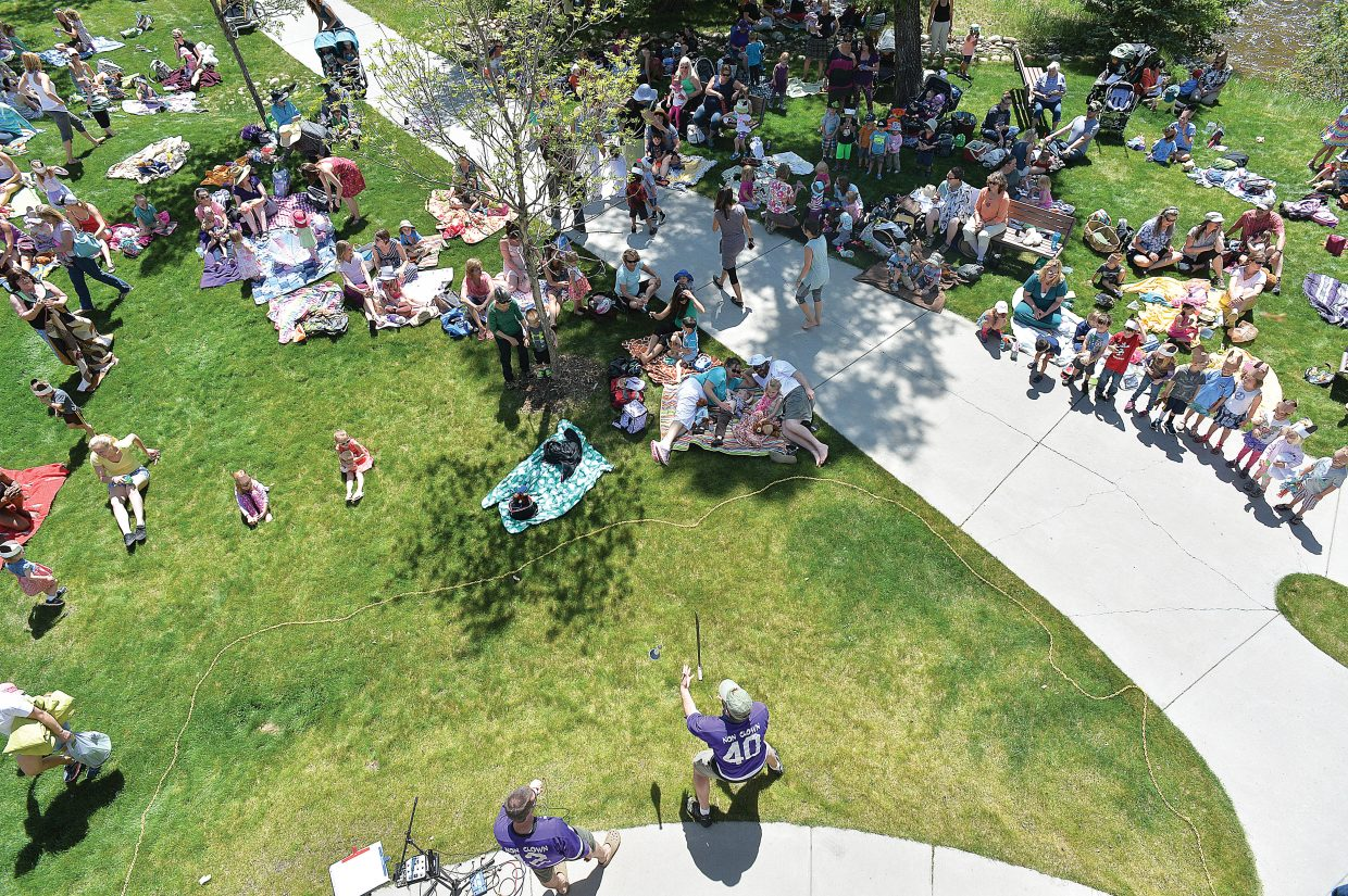Children and their caregivers gather around Scott Parker, of We're Not Clowns, performs at the annual Teddy Bear Picnic at the Bud Werner Memorial Library Thursday morning.