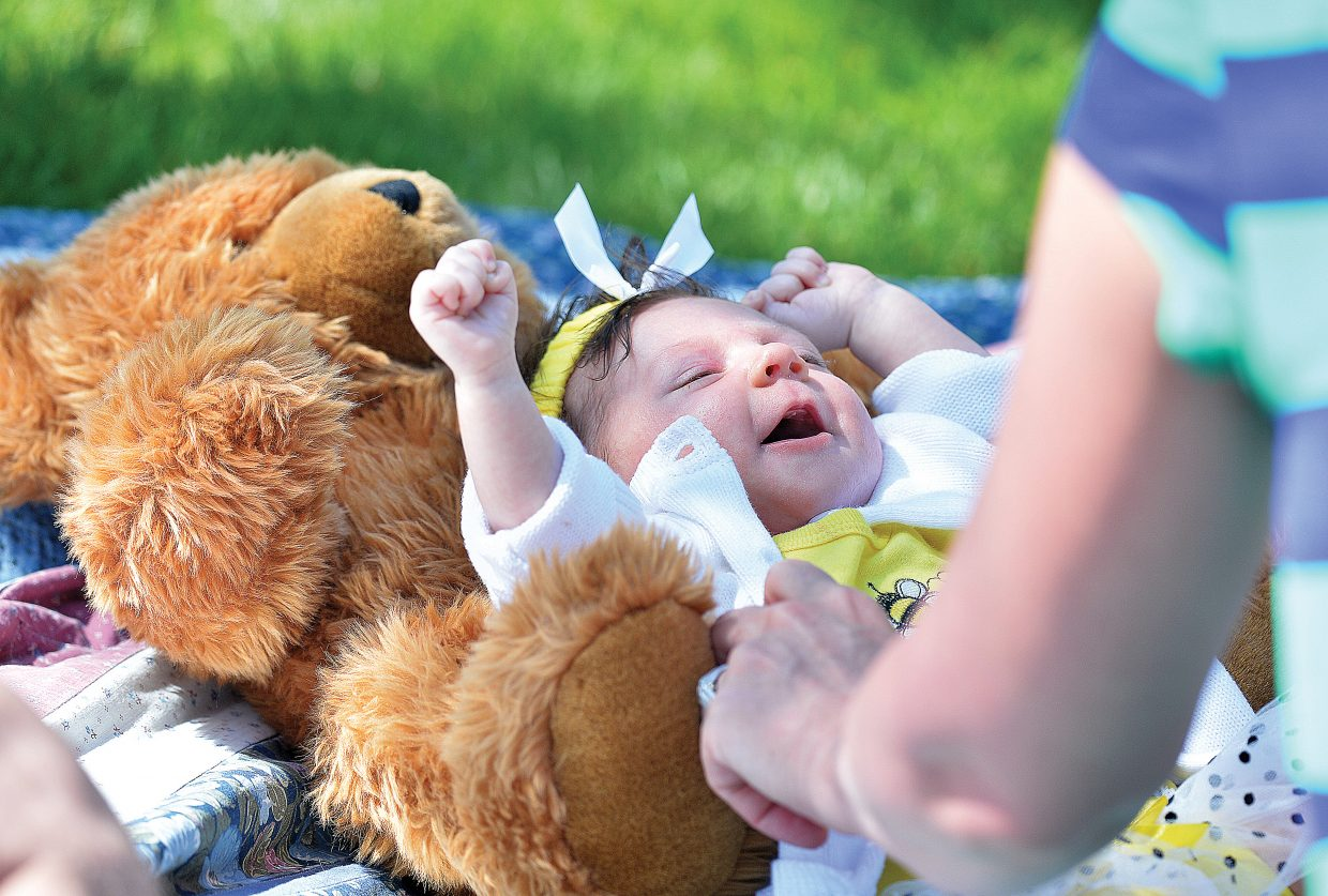 Young Inara Smith uses her Teddy Bear as a pillow while mom unbuttons her sweater at the annual Teddy Bear Picnic at the Bud Werner Memorial Library Thursday afternoon. The annual lunch has become a tradition for lots of local families in Steamboat Springs who come out for music and lunch on the lawn.