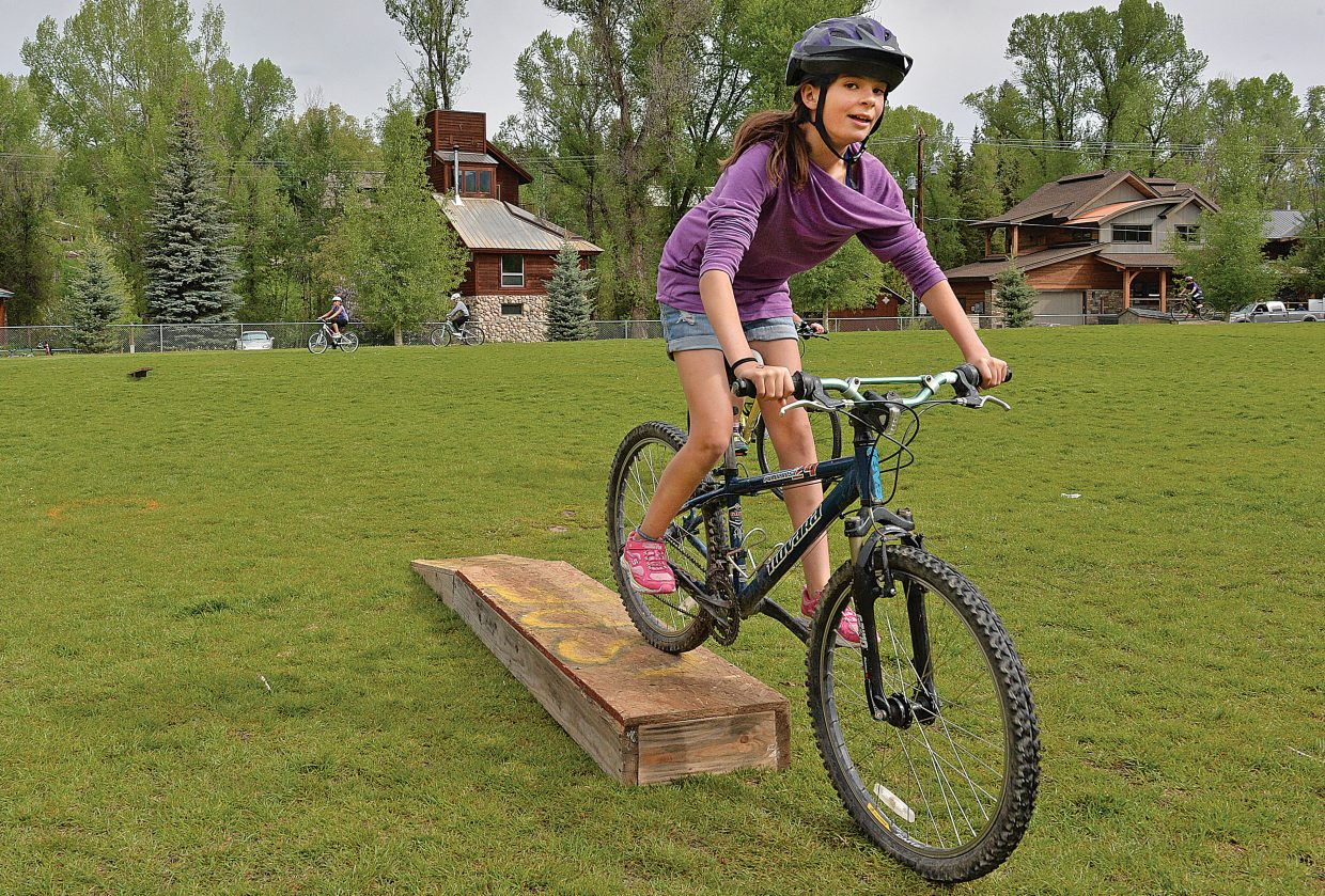 Fifth grader Alivia Thompson rides over an obstacle during the Soda Creek Elementary School's bike rally Friday morning. The bike rally featured a number of different activities designed to teach young riders the proper and safe way to take to the roads.