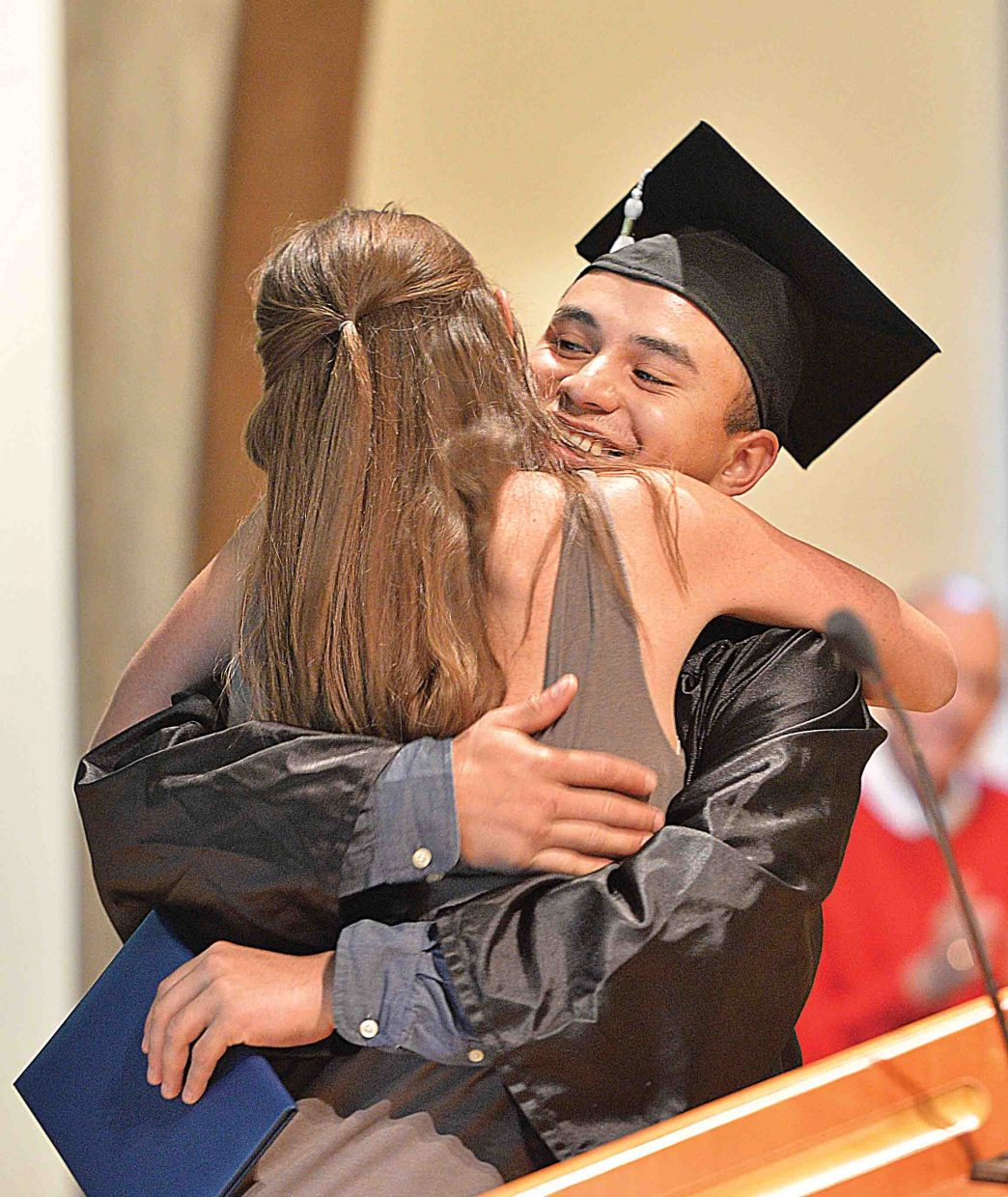 Yampa Valley High School graduating senior Jose Jimenez gets a hug from diploma presenter Molly Lotz at the school's graduation ceremony Friday afternoon at the Bud Werner Memorial Library In Steamboat Springs. The school honored eight seniors Friday as part of it's annual graduation ceremony.