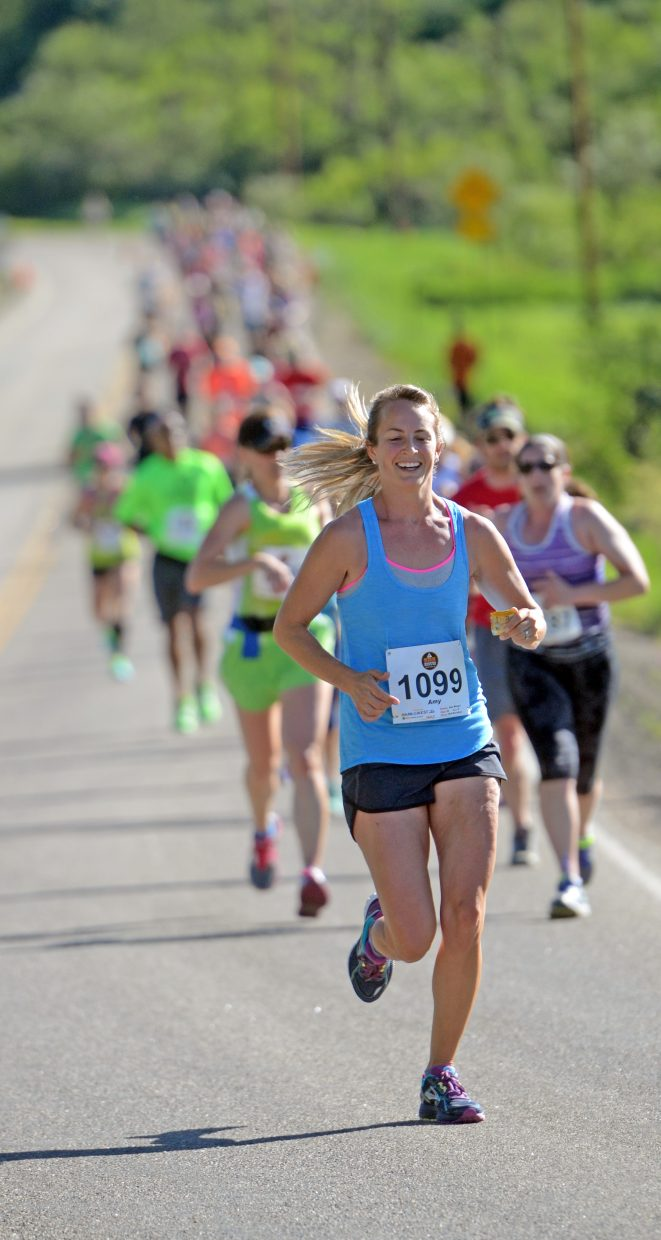 A runner smiles as she leads a pack of half-marathon runners on Sunday.