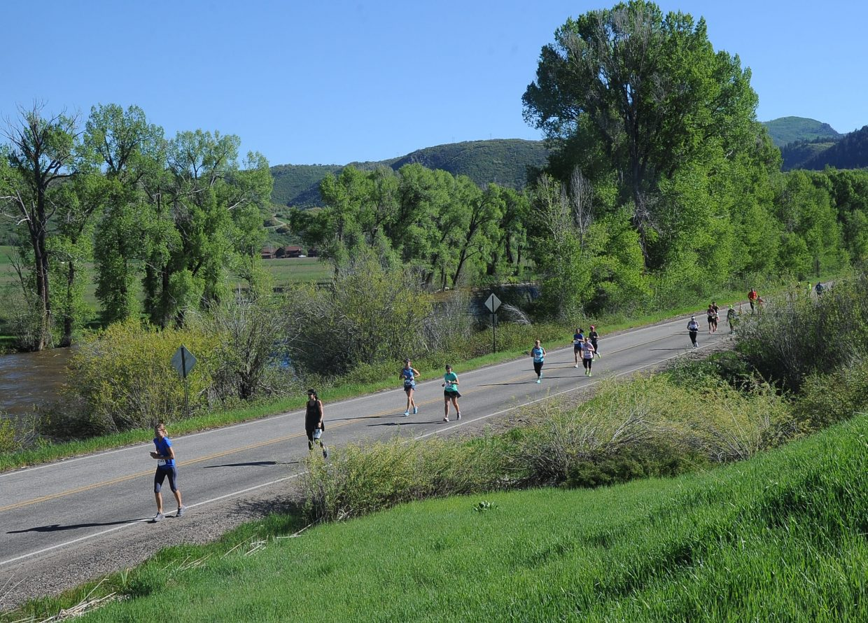 Runners in the half-marathon make their way on the course along the Elk River.