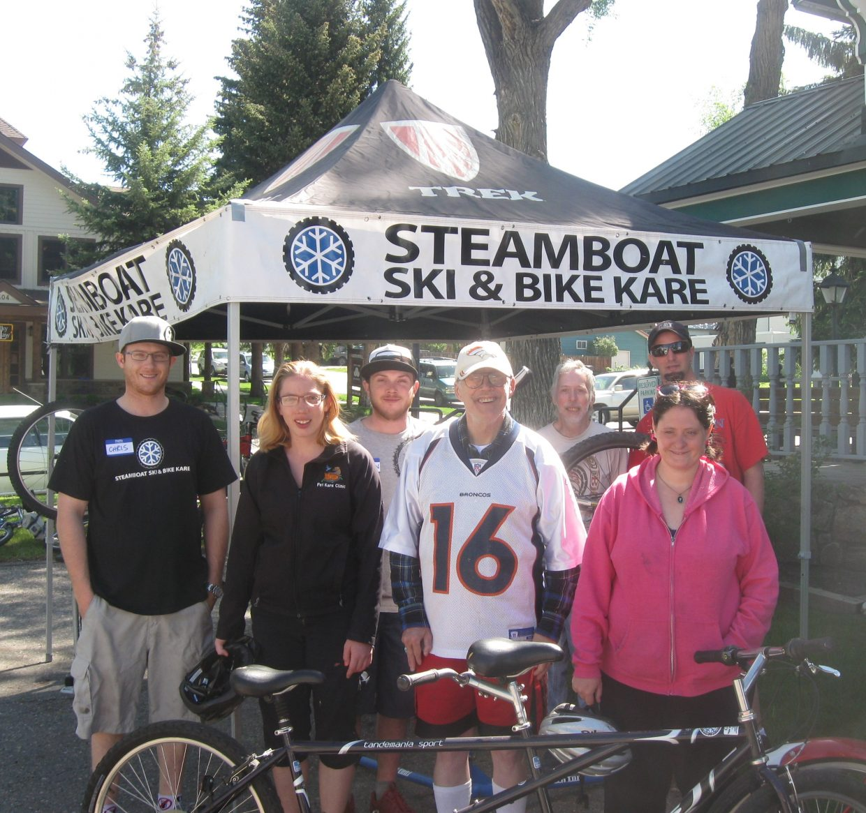 Steamboat Ski & Bike Kare technicians Chris Katers and Brandon Thorton pause to pose with a group from Horizons Specialized Services. The bike technicians volunteered their time to tune bicycles for individuals with disabilities.