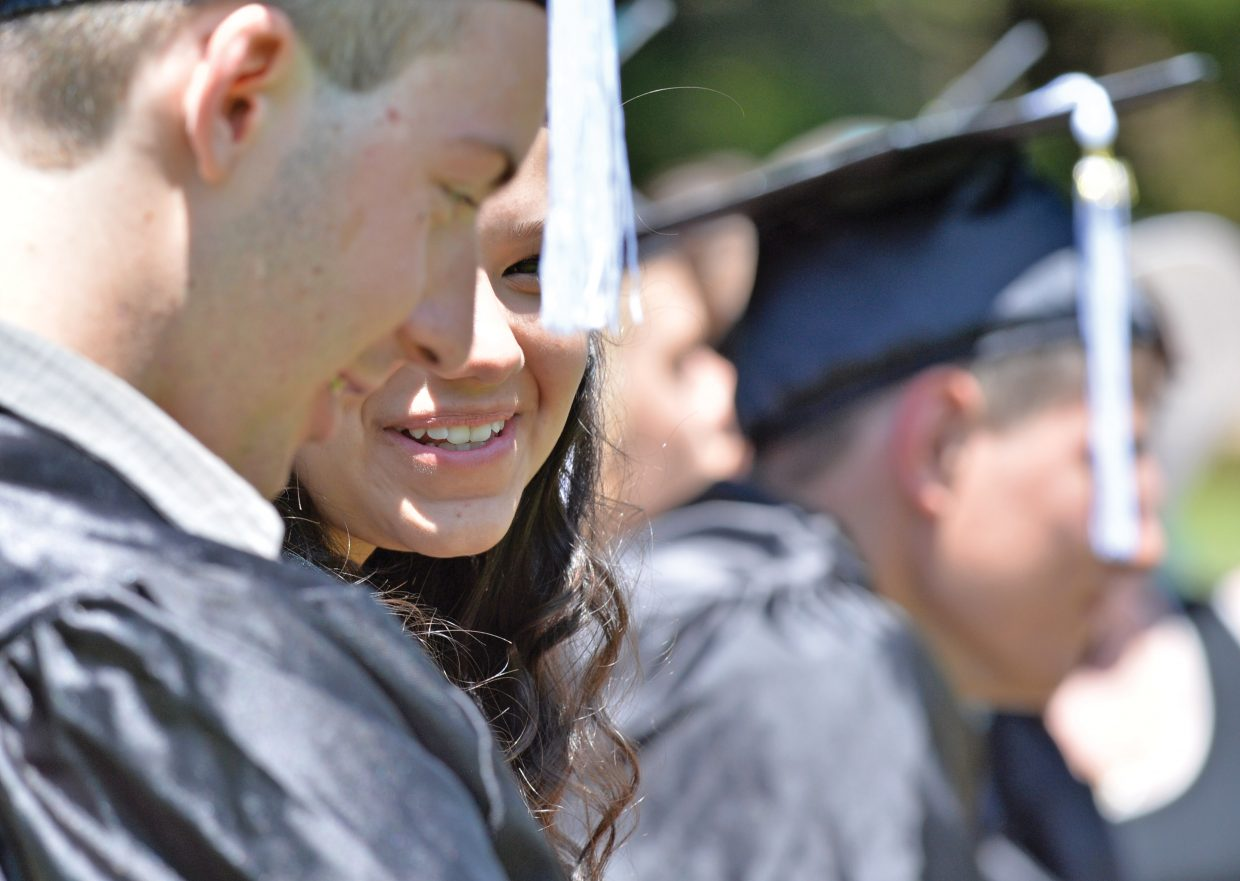 Jade Racoma smiles while listening to speakers at the 2014 Yampa Valley High School Graduation Friday afternoon at the Yampa River Botanic Park. This year's class included eight graduating seniors, seven of which were at Friday's graduation.