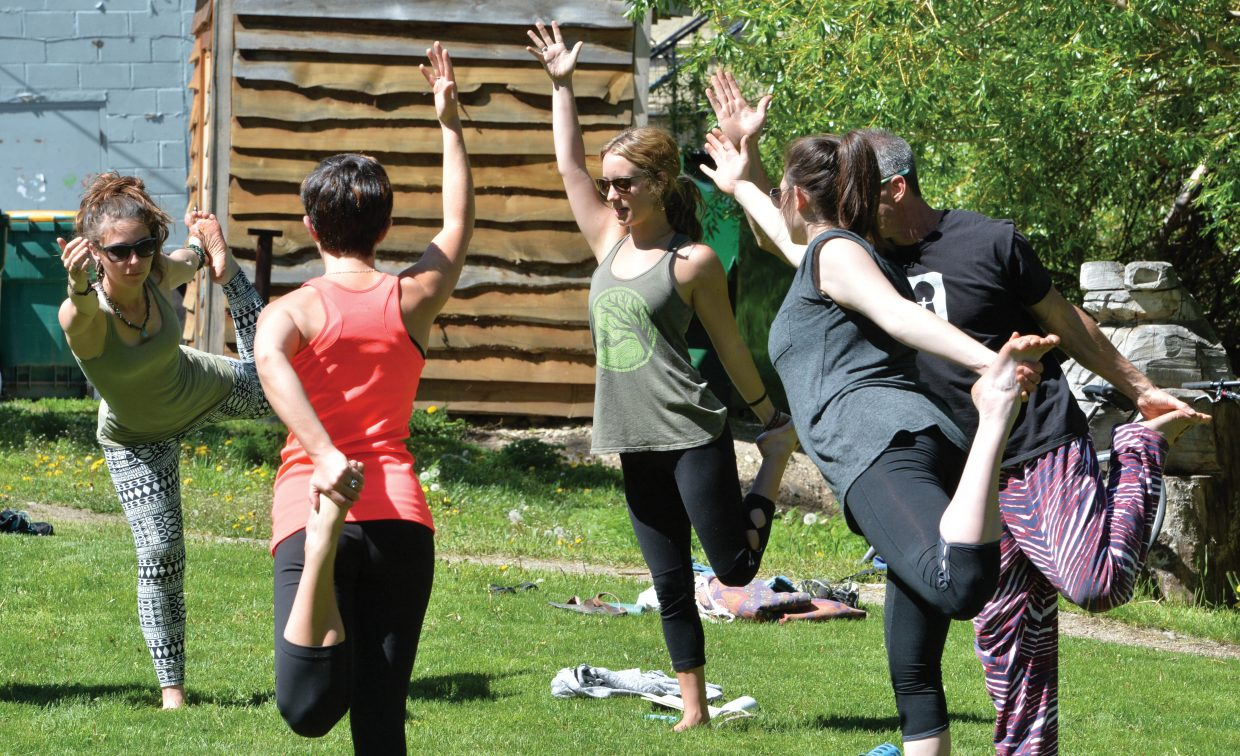 Yoga participants form a circle as they are guided by instructor Chelsea Call, middle, during a recent meeting at the Community Garden in Steamboat Springs.