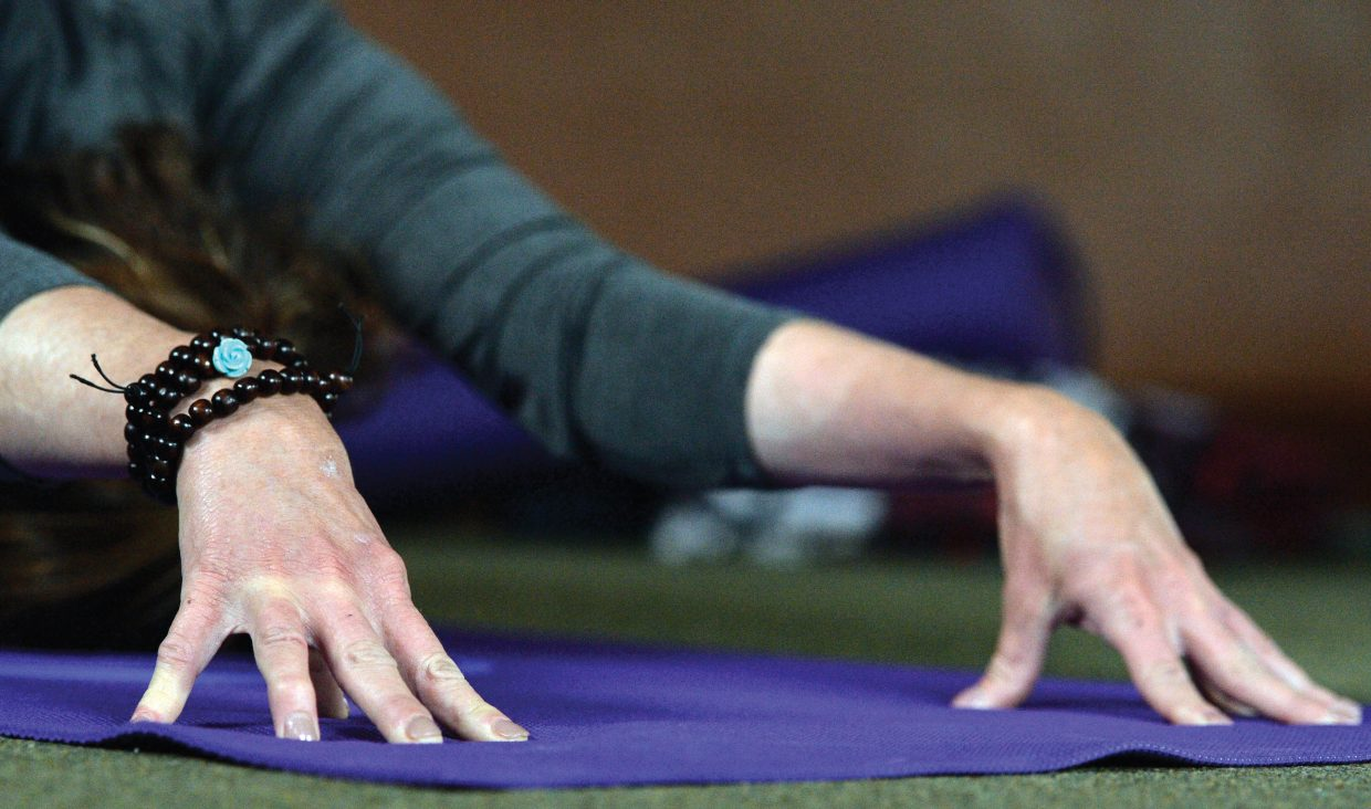Bonnie Robertson stretches her entire body, including her hands, during a class at the Yoga Center of Steamboat Springs.