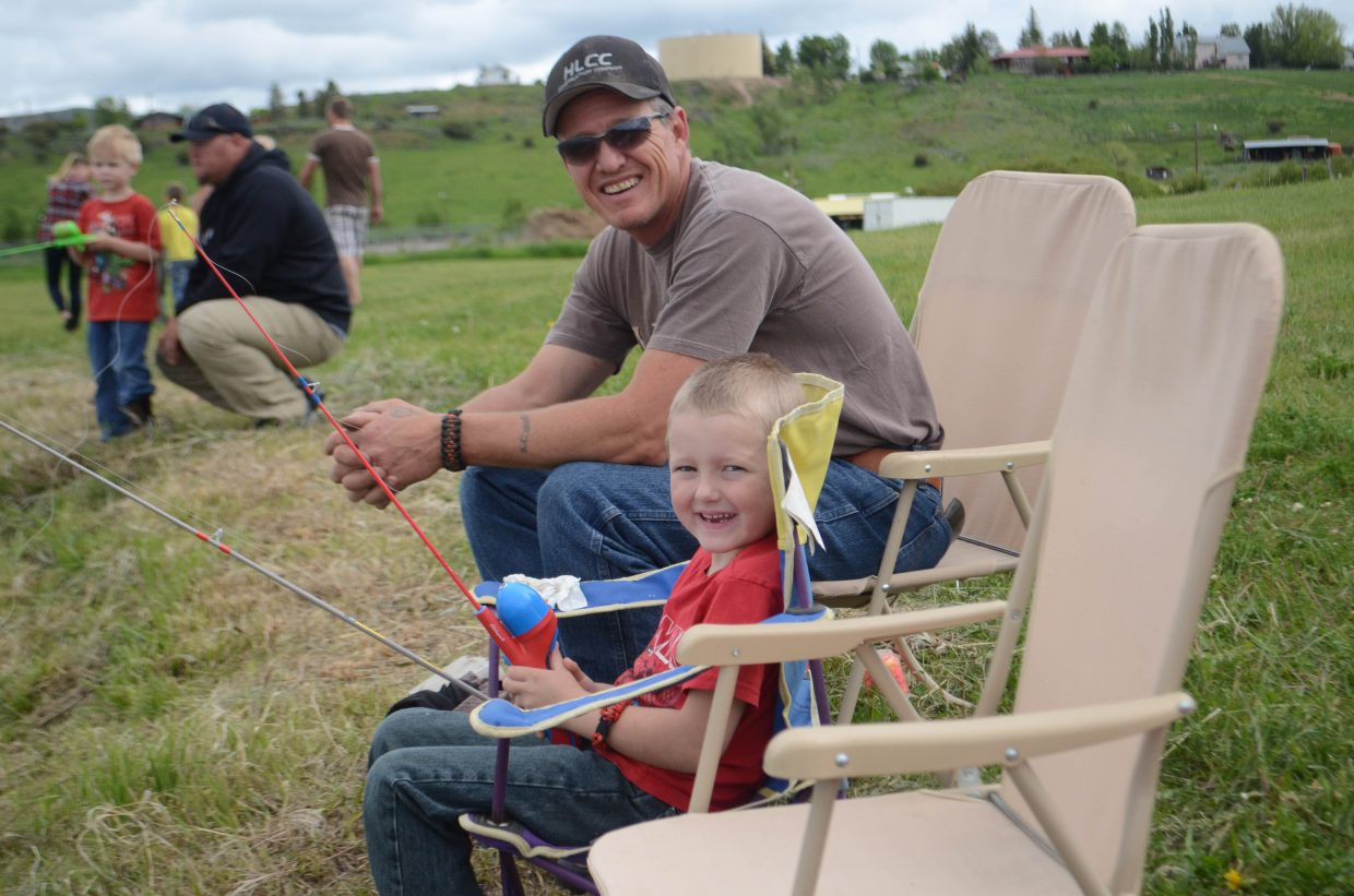 Chase Sullins, 5, and Bryan Sullins, are all smiles during Saturday's Huck Finn Day Fishing Derby at Hayden's Dry Creek Park.