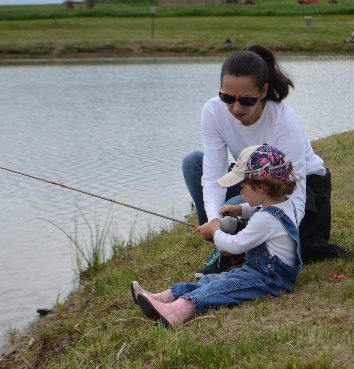 Eve Phillips, of Craig, helps Courtney Archuleta reel in her line during Saturday's Huck Finn Day Fishing Derby at Hayden's Dry Creek Park.