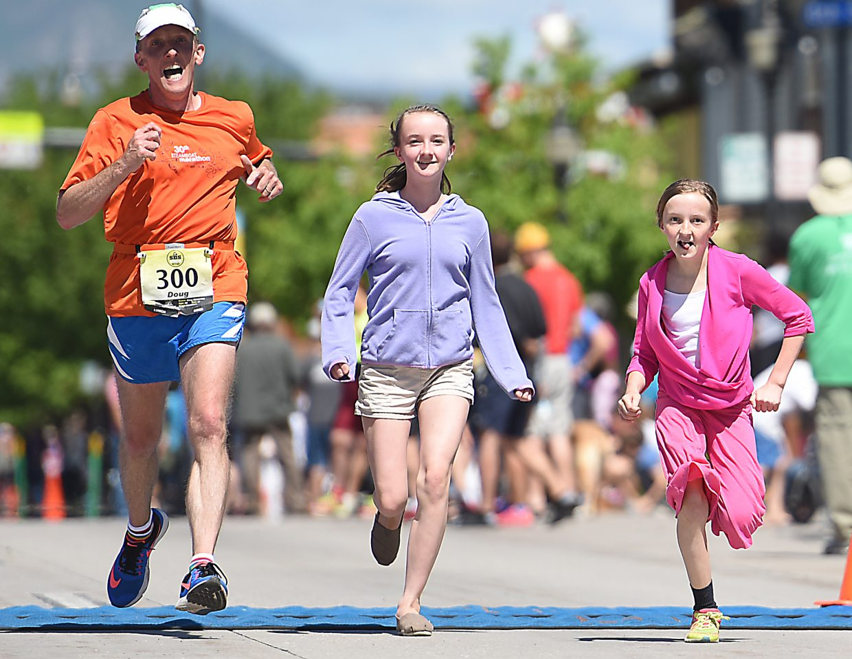Doug Spannring flies toward the finish line of the Steamboat Marathon, encouraged on by his children, Olivia, 10, right, and Elizabeth, 12.