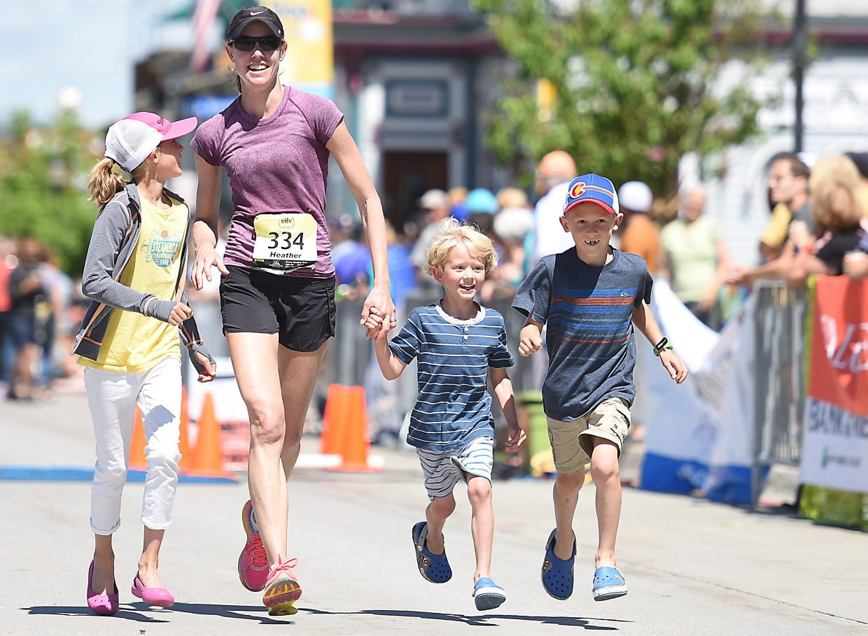 Heather Vieth runs toward the finish line with her children, Stella, Jack and Max, on Sunday at the Steamboat Marathon.