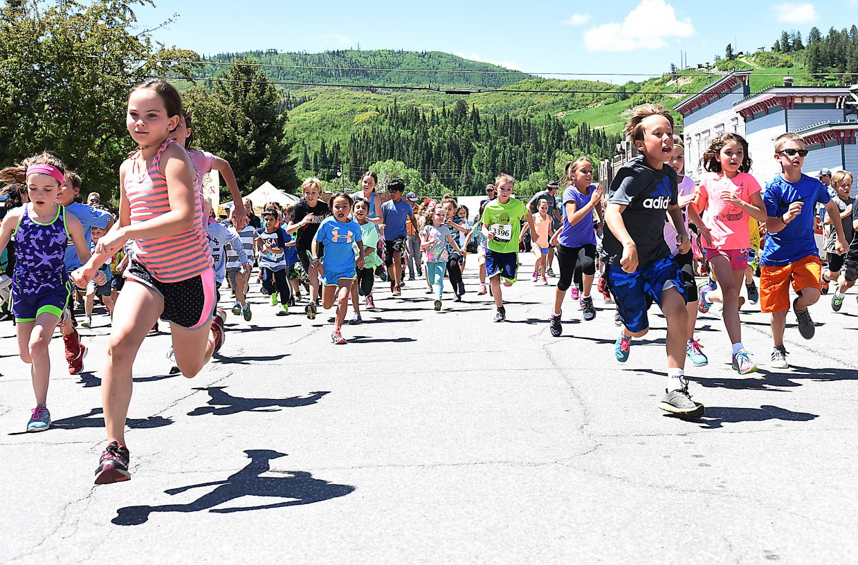 Runners sprint from the finish line Sunday during a kid's fun run Sunday at the Steamboat Marathon.