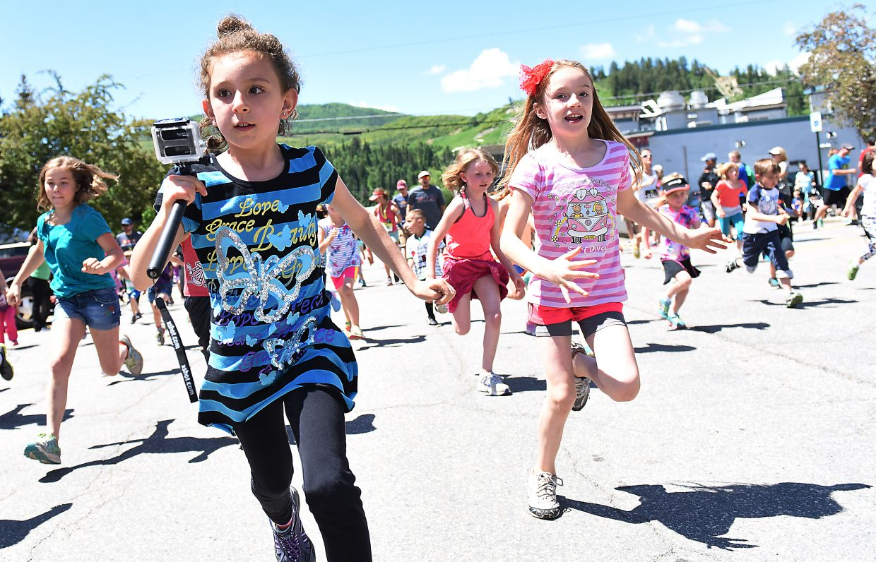A runner documents her journey during a kid's fun run Sunday at the Steamboat Marathon.