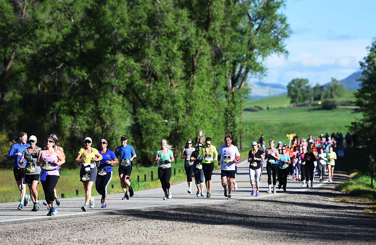 A group of runners heads down the road Sunday during the Steamboat Marathon.