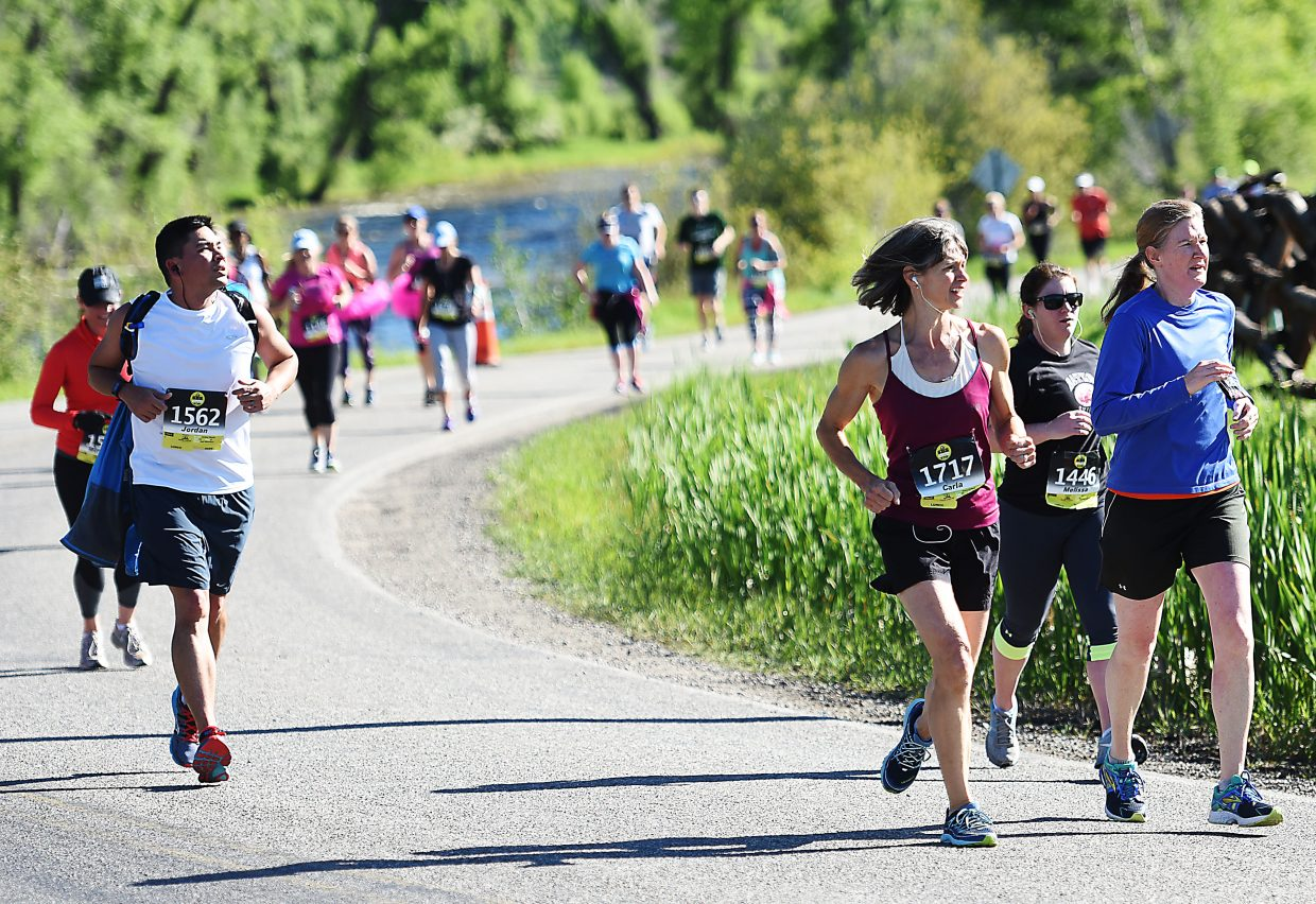 Runners look toward Steamboat Springs as they round a corner during the annual Steamboat Marathon on Sunday.
