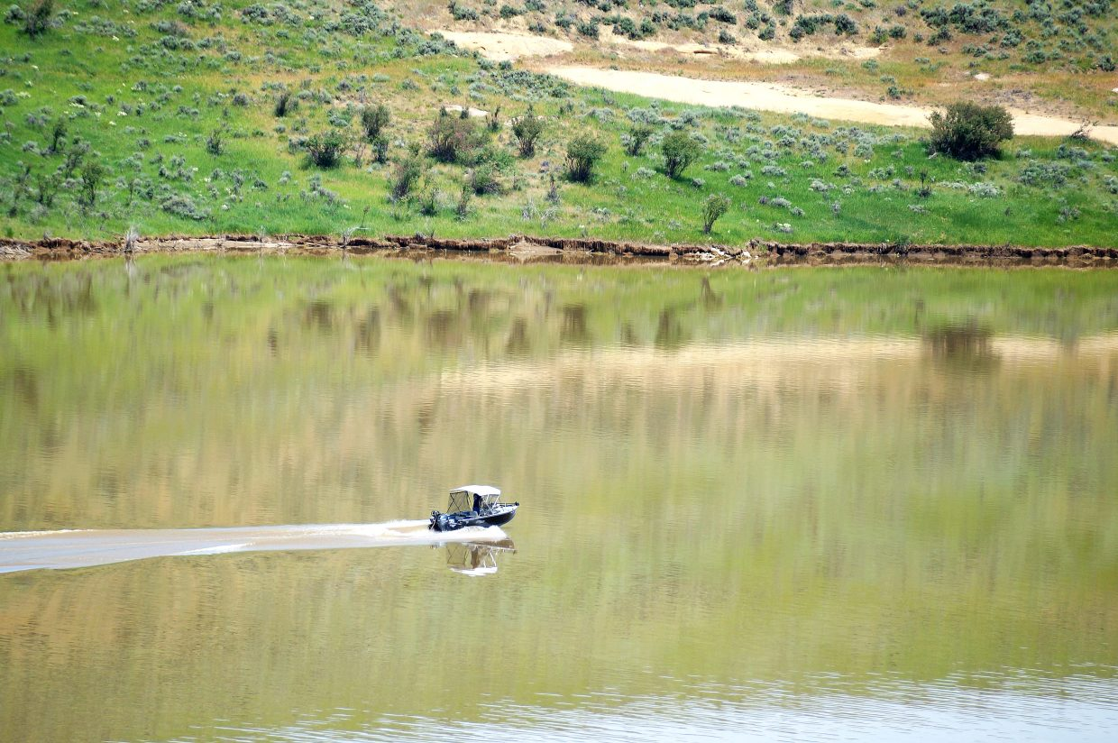 A boat cruises the waters at Elkhead Reservoir Tuesday morning. Come Saturday, the reservoir is slated to be filled with boats for a fishing tournament, aimed at catching a large chunk of non-native species.