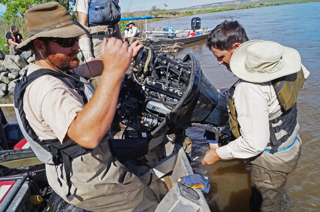 Noble and Mike Partlow, CPW fishery technician, work on a mechanical issue on one of the shock boat's motors. The boat ended up out of commission for the day.