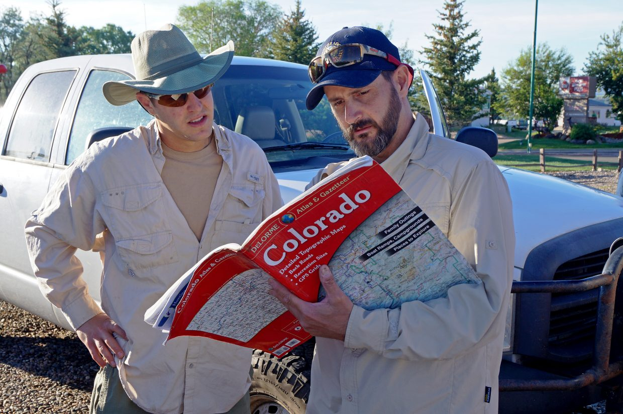 Before leaving the parking lot of their hotel, CPW biologist Cory Noble gives fishery technician Drew Reynolds directions to the launch ramp.