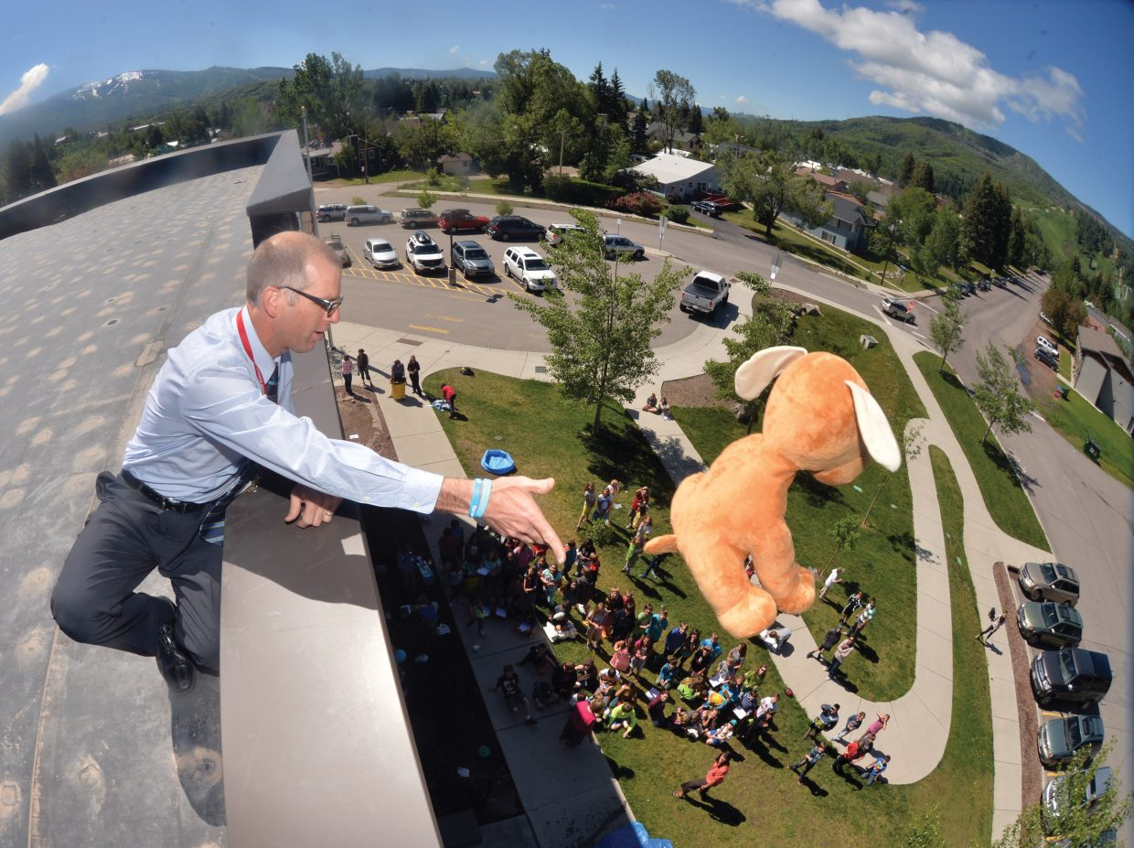 Soda Creek Elementary fifth-grade teacher Andrew Miller pushes a stuffed animal containing an egg off the roof of the downtown school during the annual egg drop. Fifth-graders designed and built the crafts with the purpose of protecting an uncooked egg from the nearly two-story drop. Student Miranda Apodaca hid the egg inside a stuffed animal.