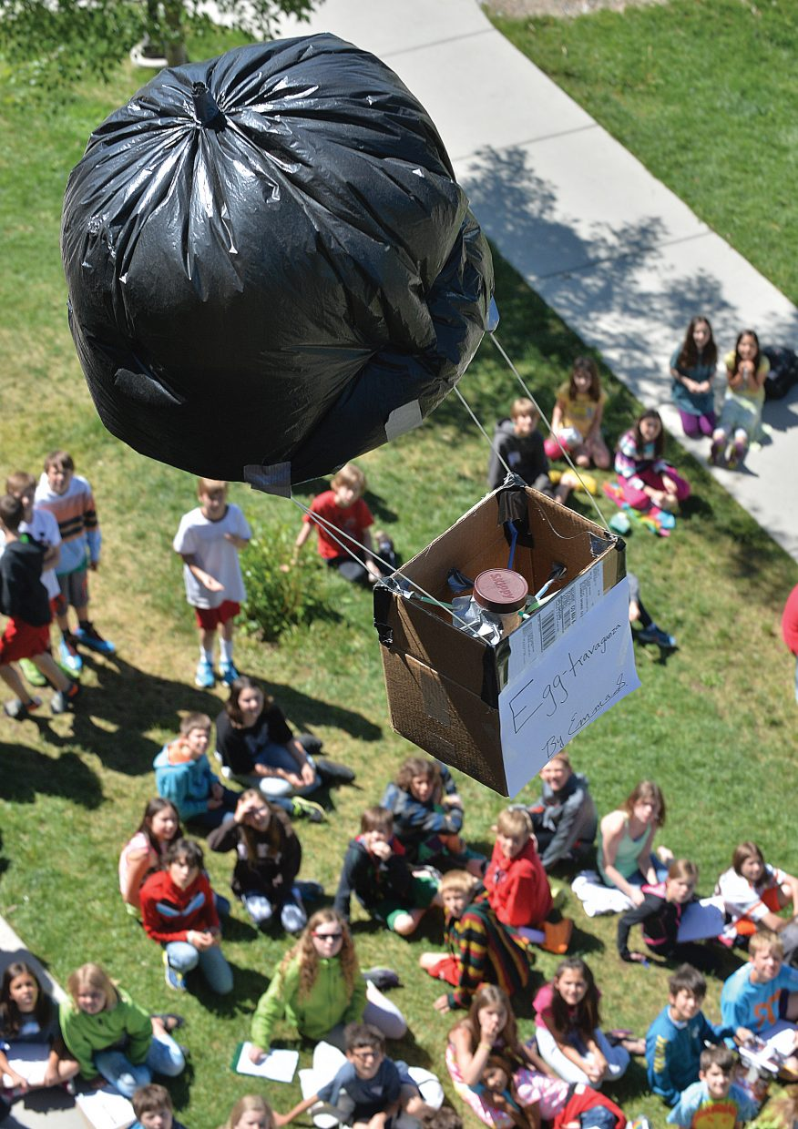 Soda Creek Elementary fifth-graders watch as this egg craft floats toward the ground during the annual egg drop at the school Monday morning. Fifth-graders designed and built the crafts with the purpose of protecting an uncooked egg from the nearly two-story drop.