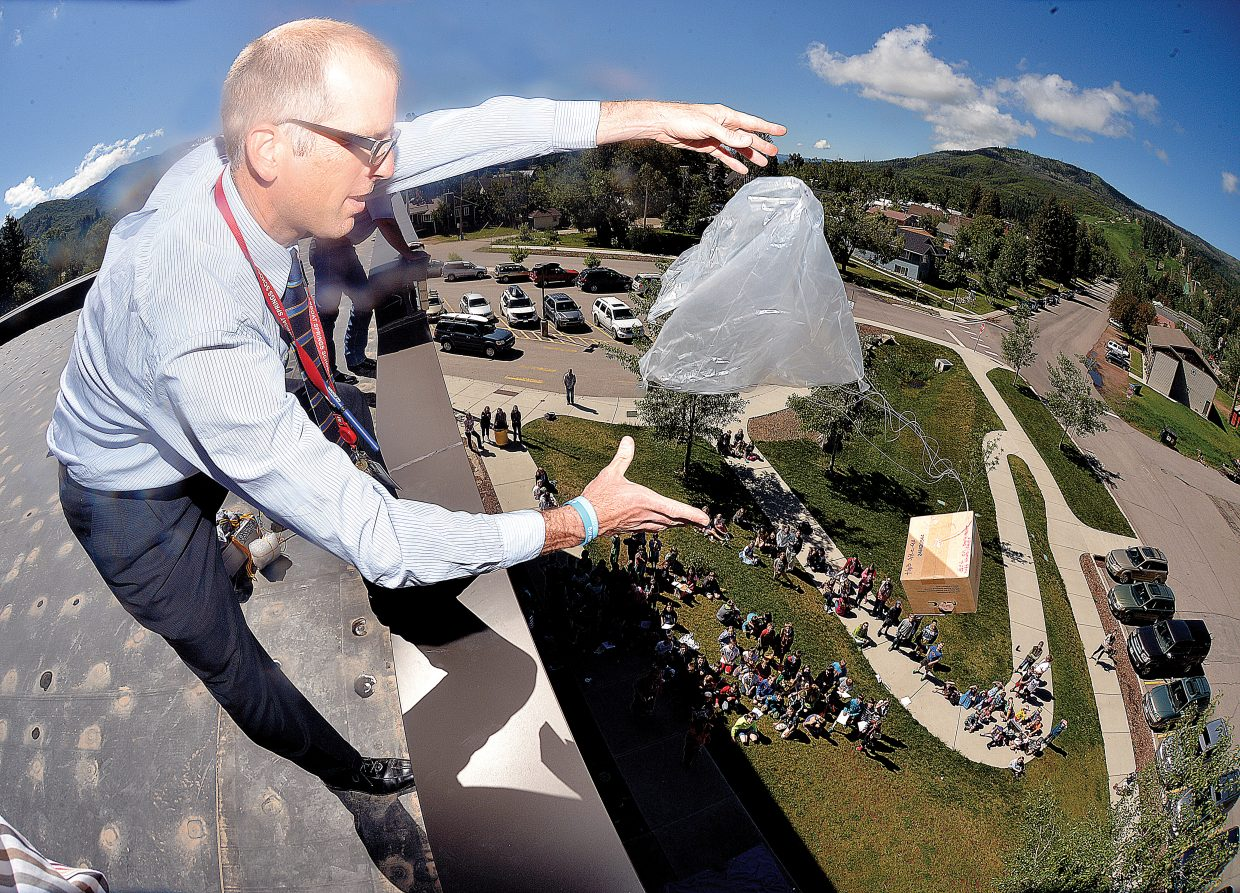 Soda Creek Elementary fifth-grade teacher Andrew Miller launches a protective craft off the top of the building during the annual egg drop at the school Monday morning. Fifth-graders designed and built the crafts with the purpose of protecting an uncooked egg from the nearly two-story drop.