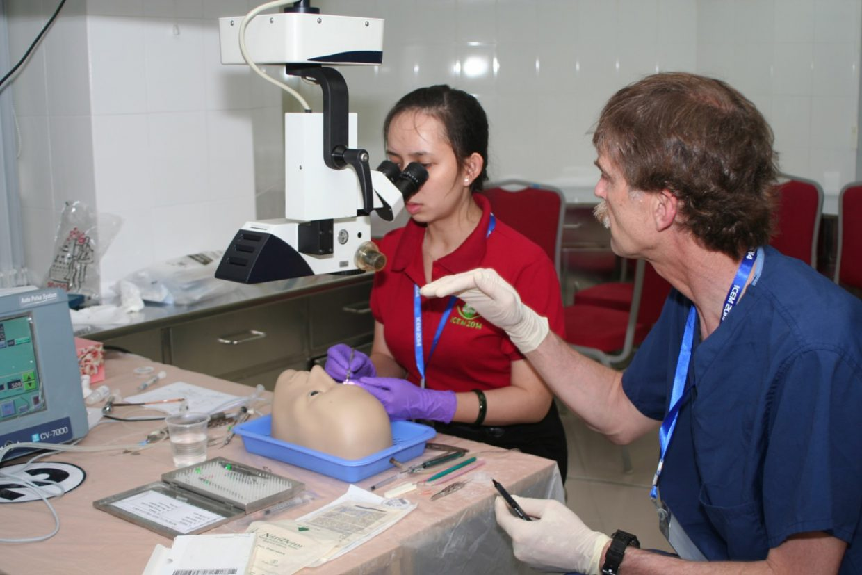 Steamboat Springs eye doctor Mark Helm helps Dr Viet Lien prepare a lens implant used in cataract surgery. Helm called his trip to Vietnam to teach cataract surgery one of the most rewarding experiences of his medical career.