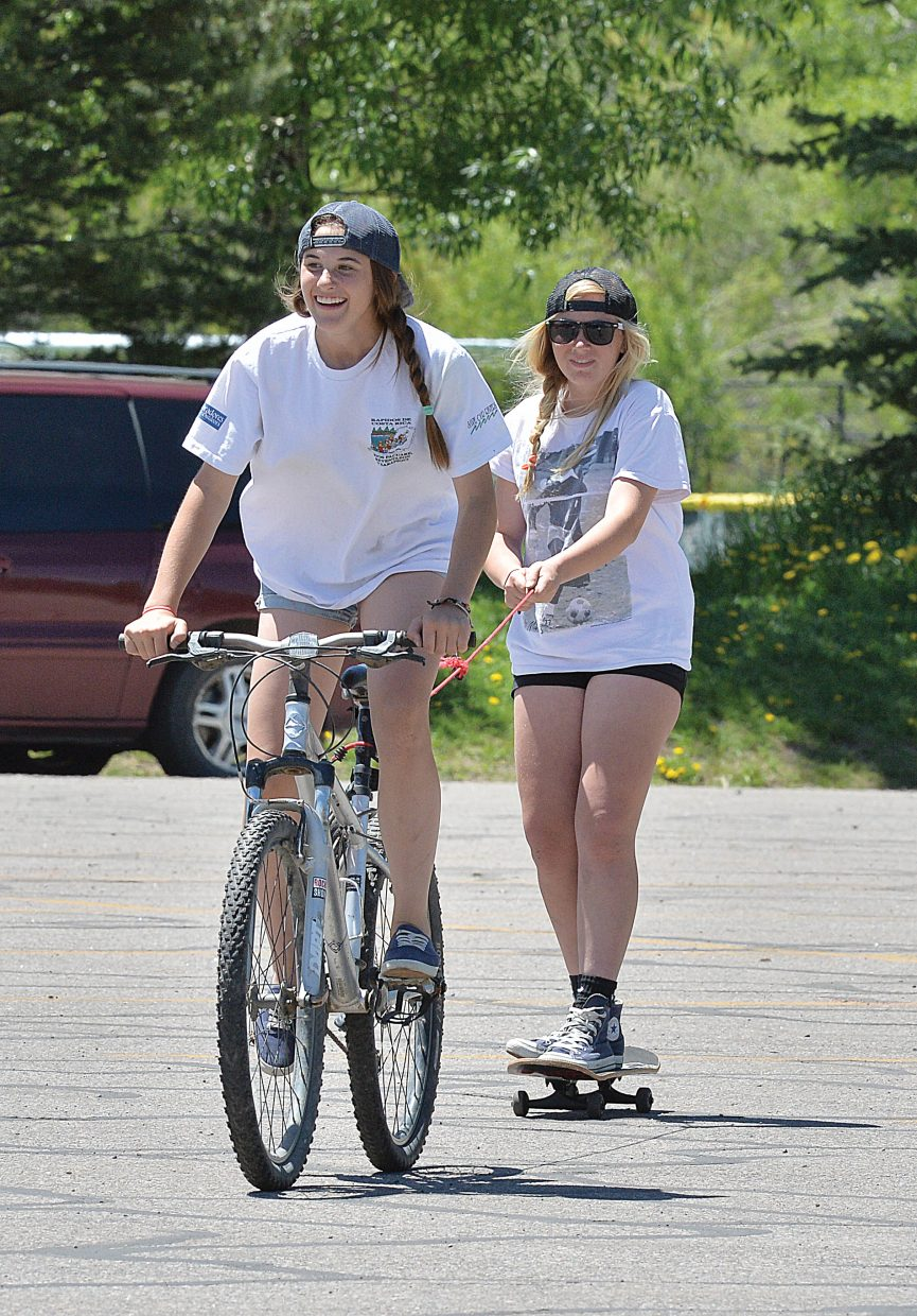 Kelly Petix, on bike, and Lauren Graham kill some time bike surfing at the Emerald Park parking lot last week.
